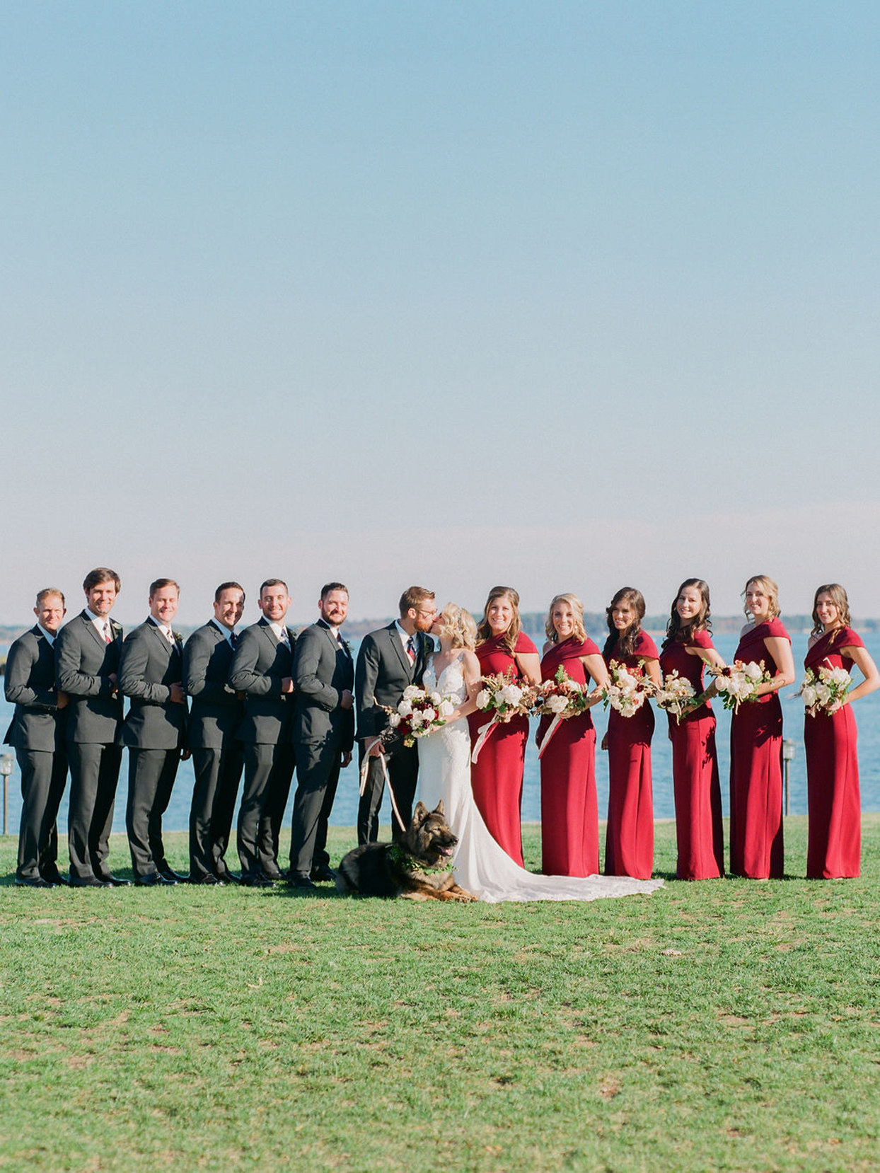 wedding party with bridesmaids in red dresses and groomsmen in black tuxes