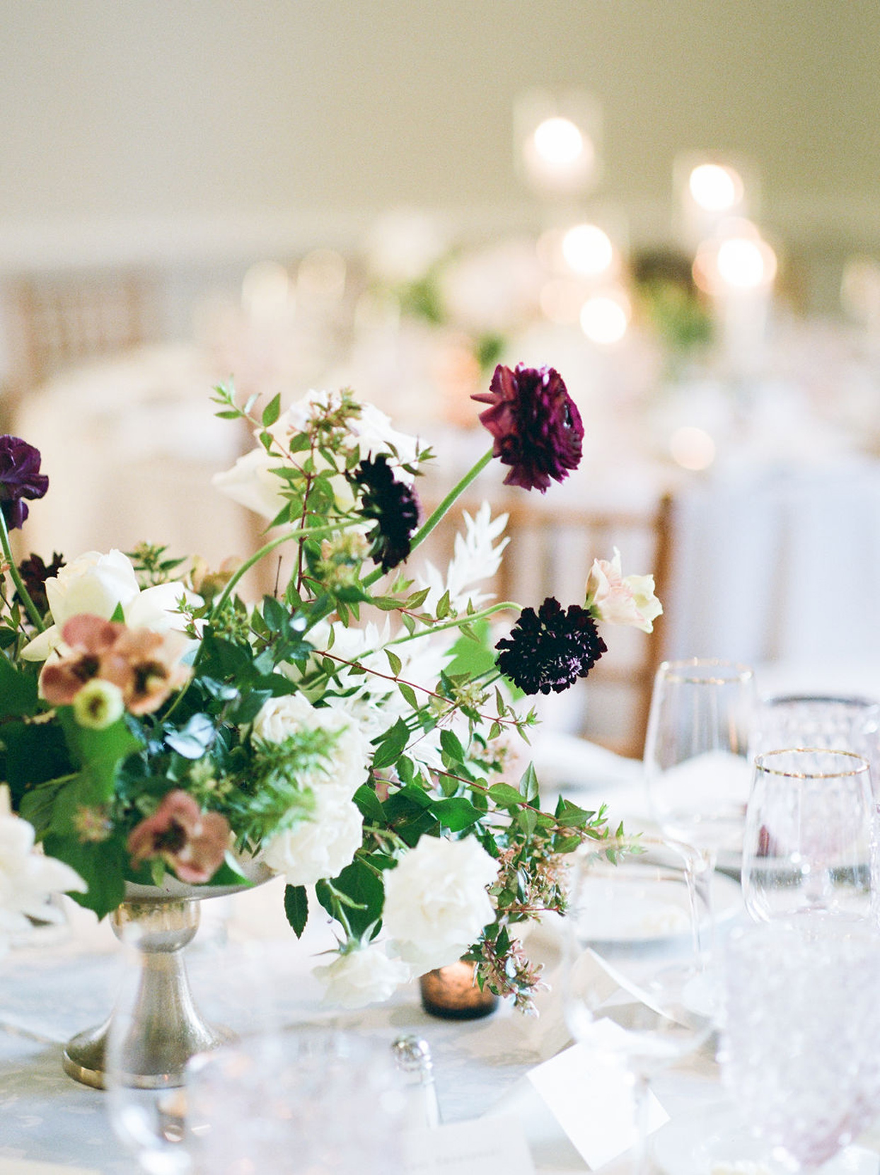 reception table setting with floral arrangement in silver vase