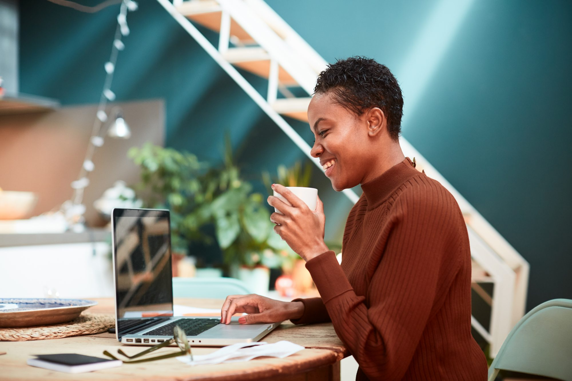 smiling woman with coffee cup looking at computer