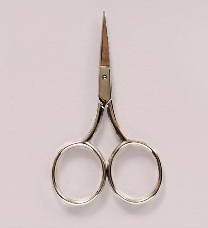 small pointed scissors on pink background