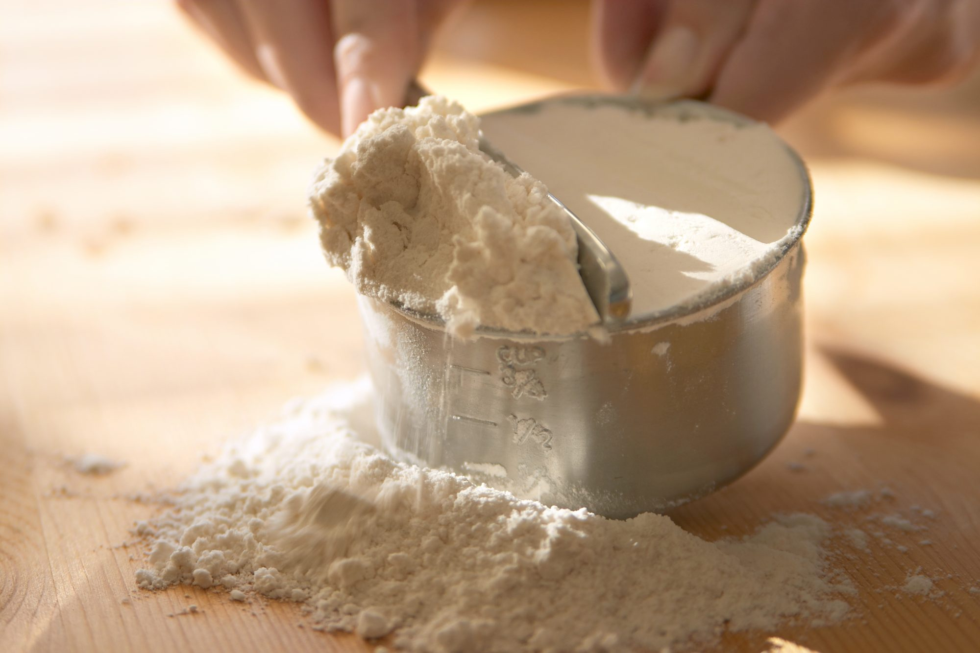 discarding extra flour from measuring cup