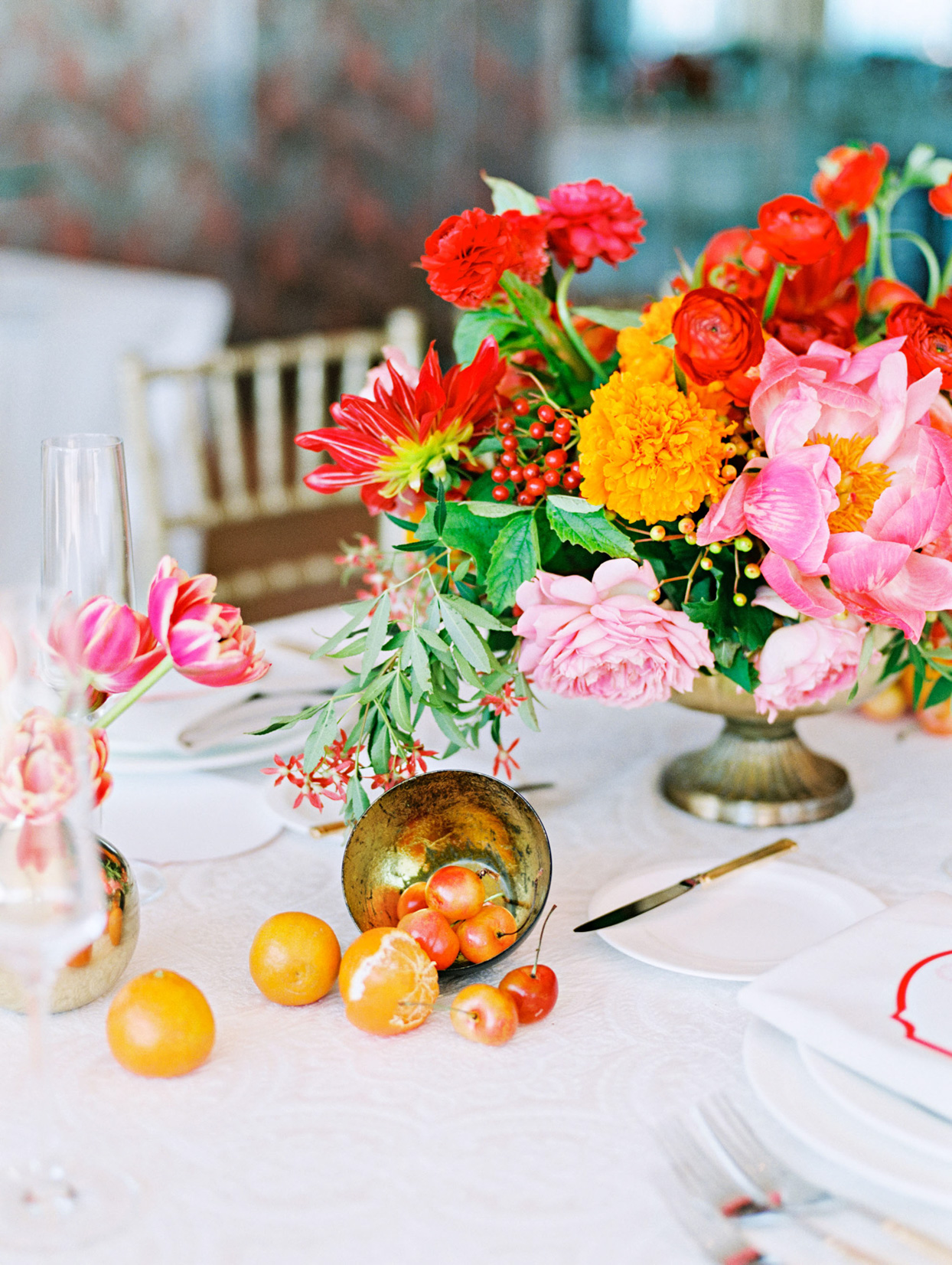 Centerpiece with dahlias, roses, marigolds, ranunculus, berries, snapdragons, and fruit