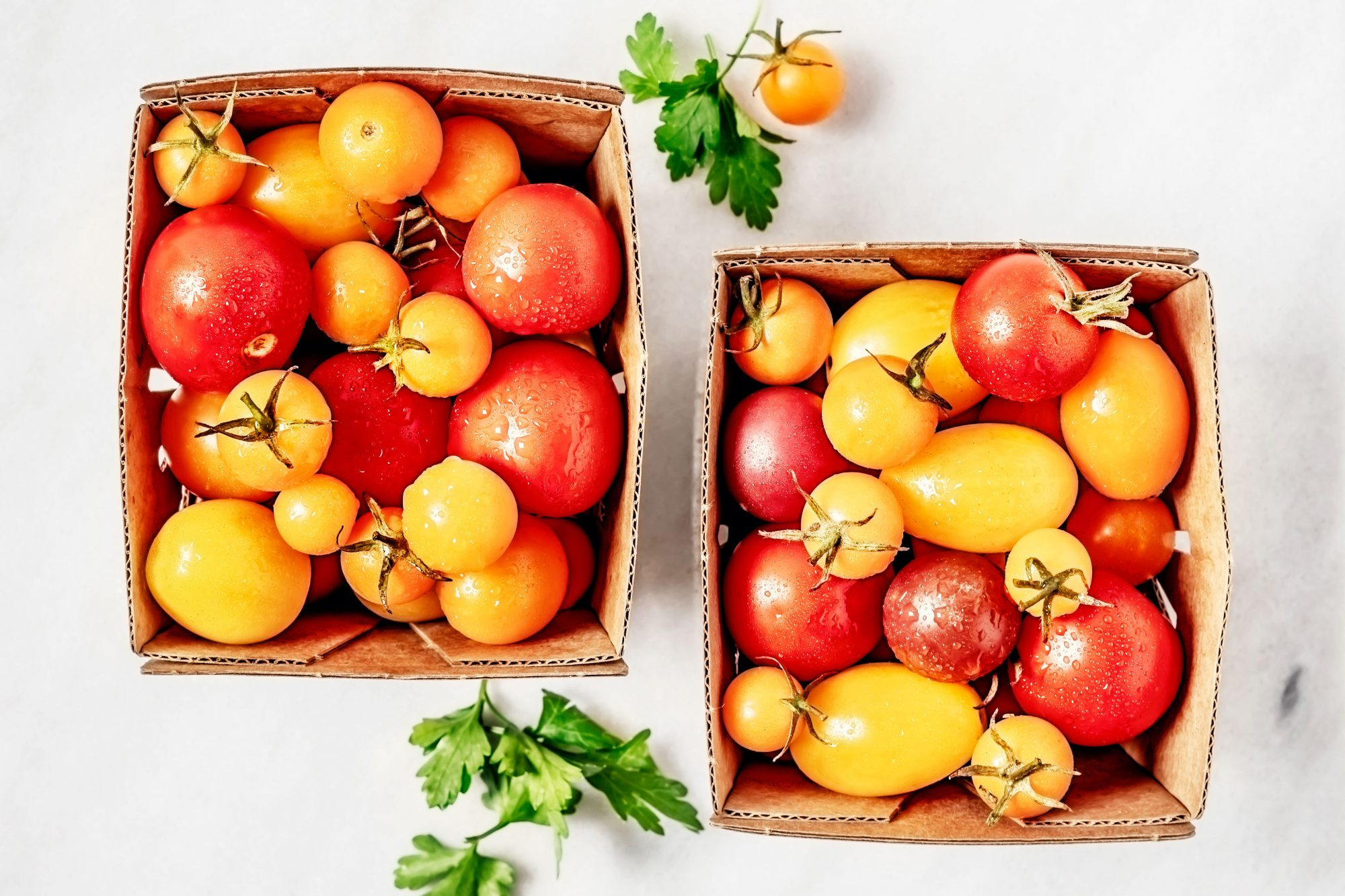 two baskets of colorful small tomatoes