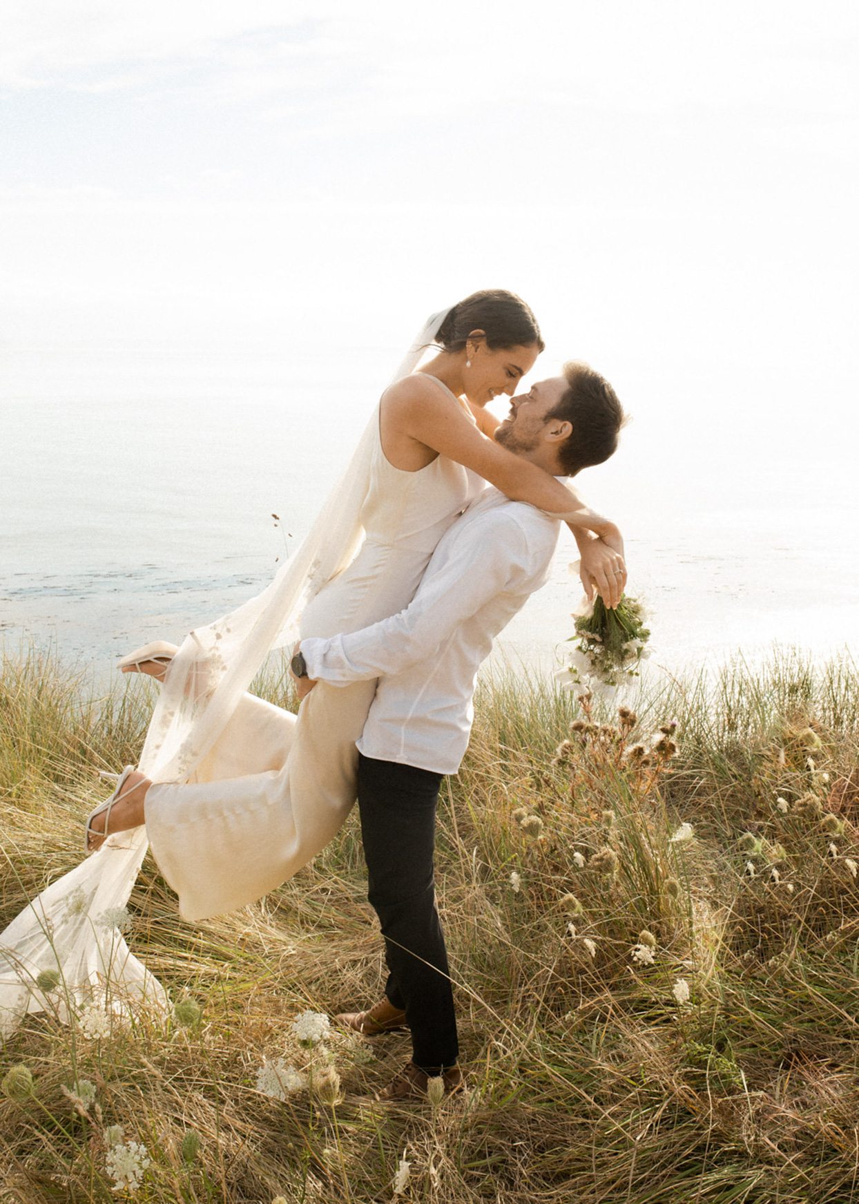 Bride and groom in grass near beach