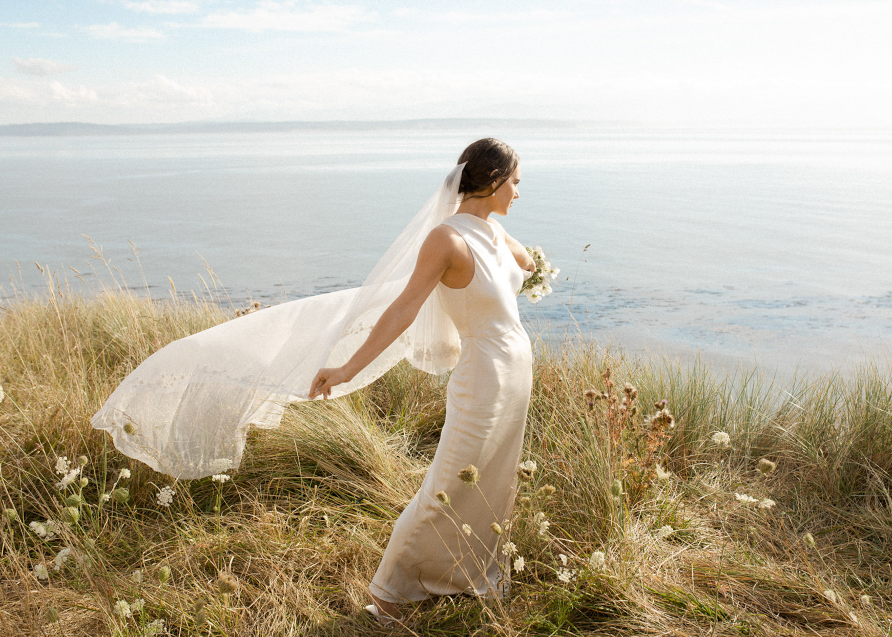 bride standing in grass near beach