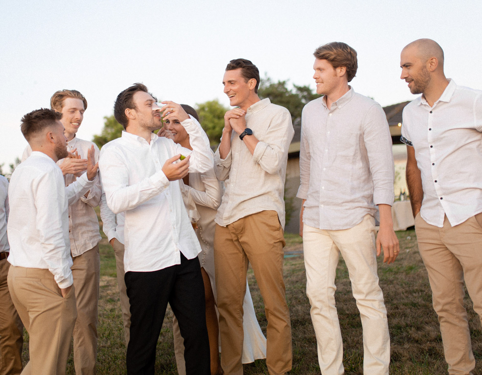 groom with groomsmen in tan pants and white shirts