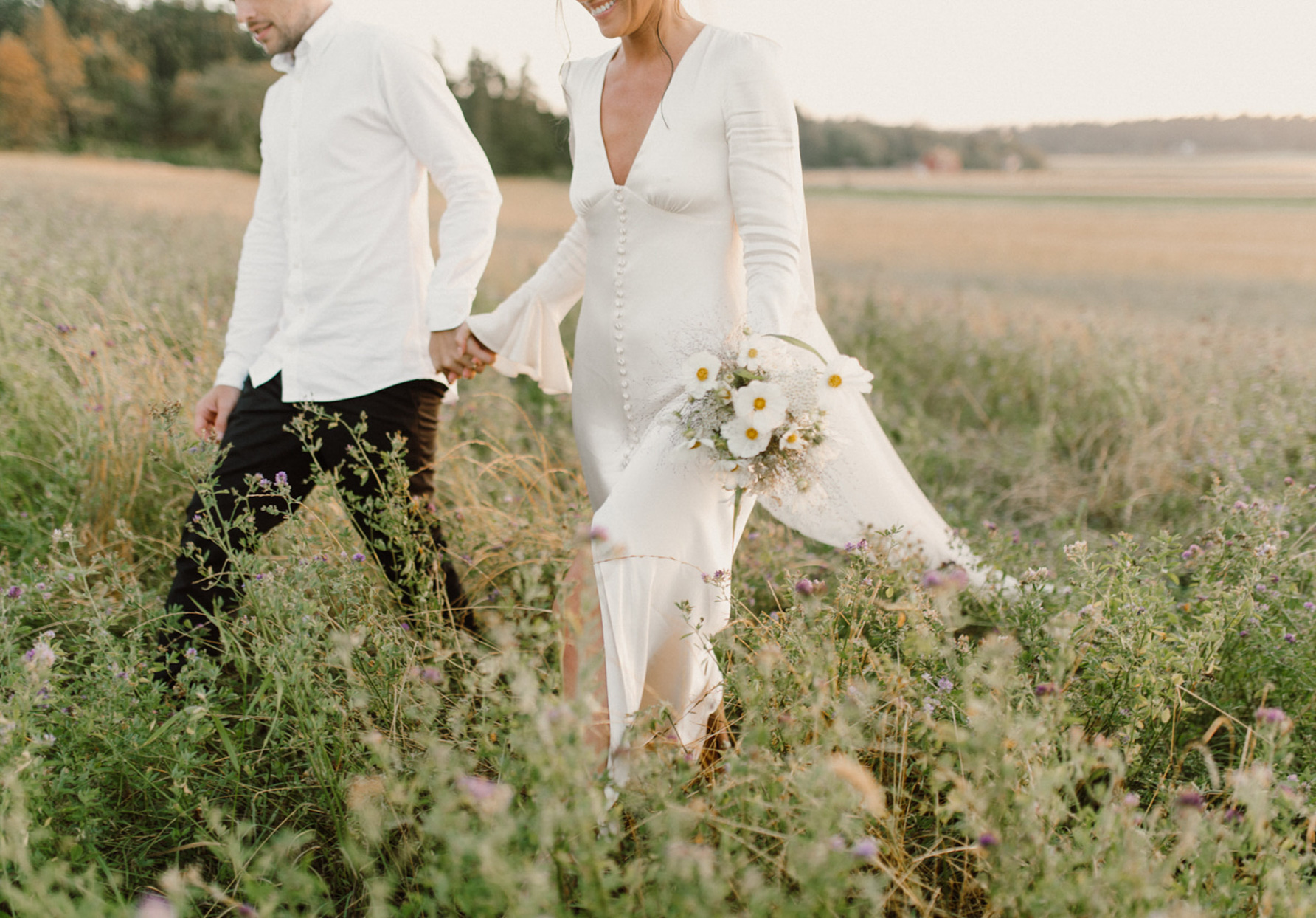 bride and groom holding hands in grass