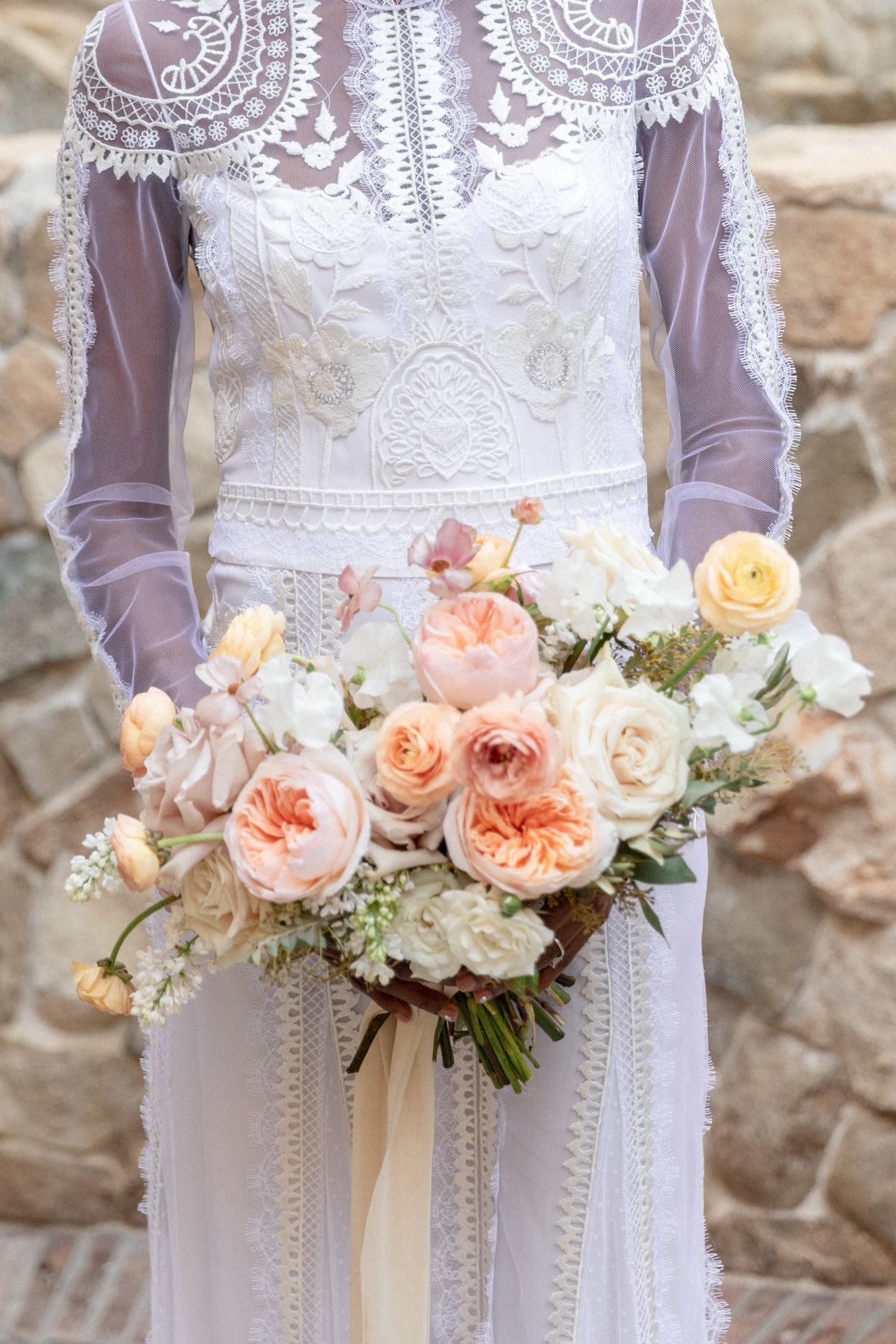 bride holding blush toned wide wedding bouquet