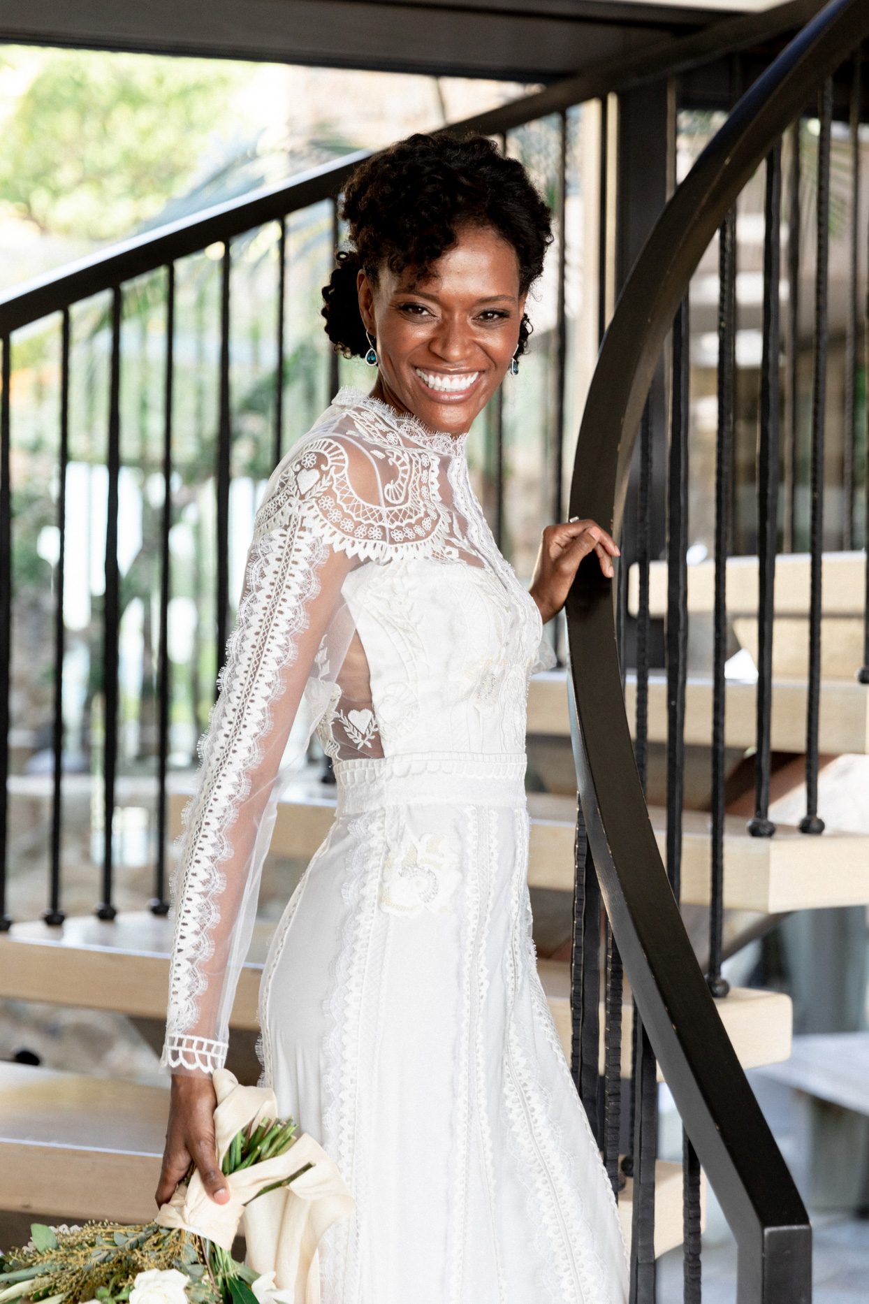 bride smiling on black staircase in high neck long sleeve dress