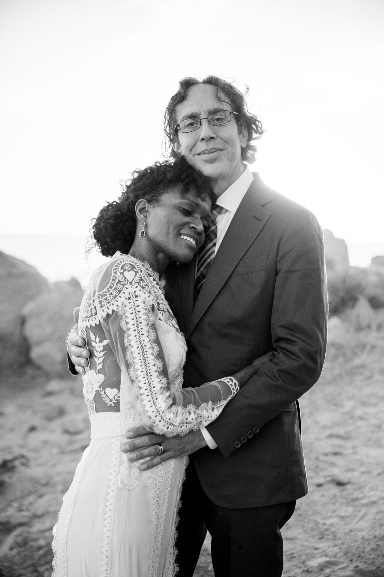 bride and groom embrace smiling on rocky beach
