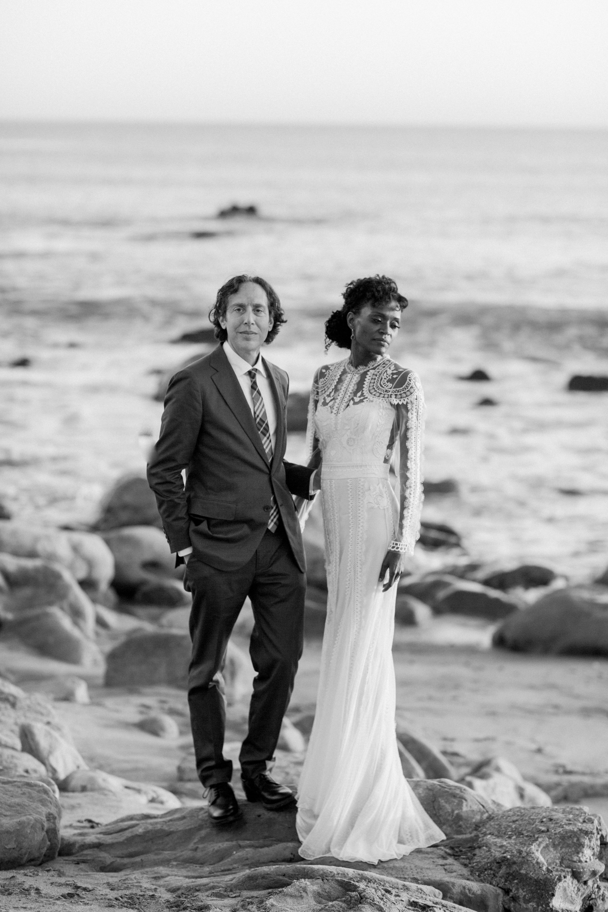 bride and groom standing on rocky beach area by ocean