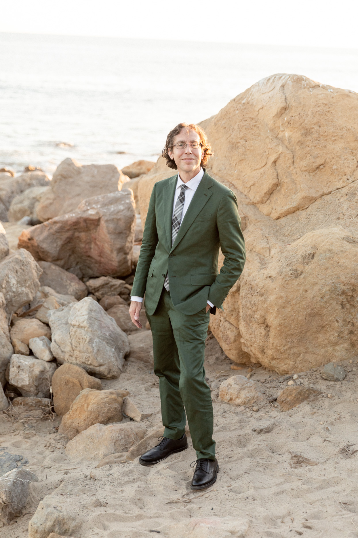 groom wearing olive green wedding suit on beach