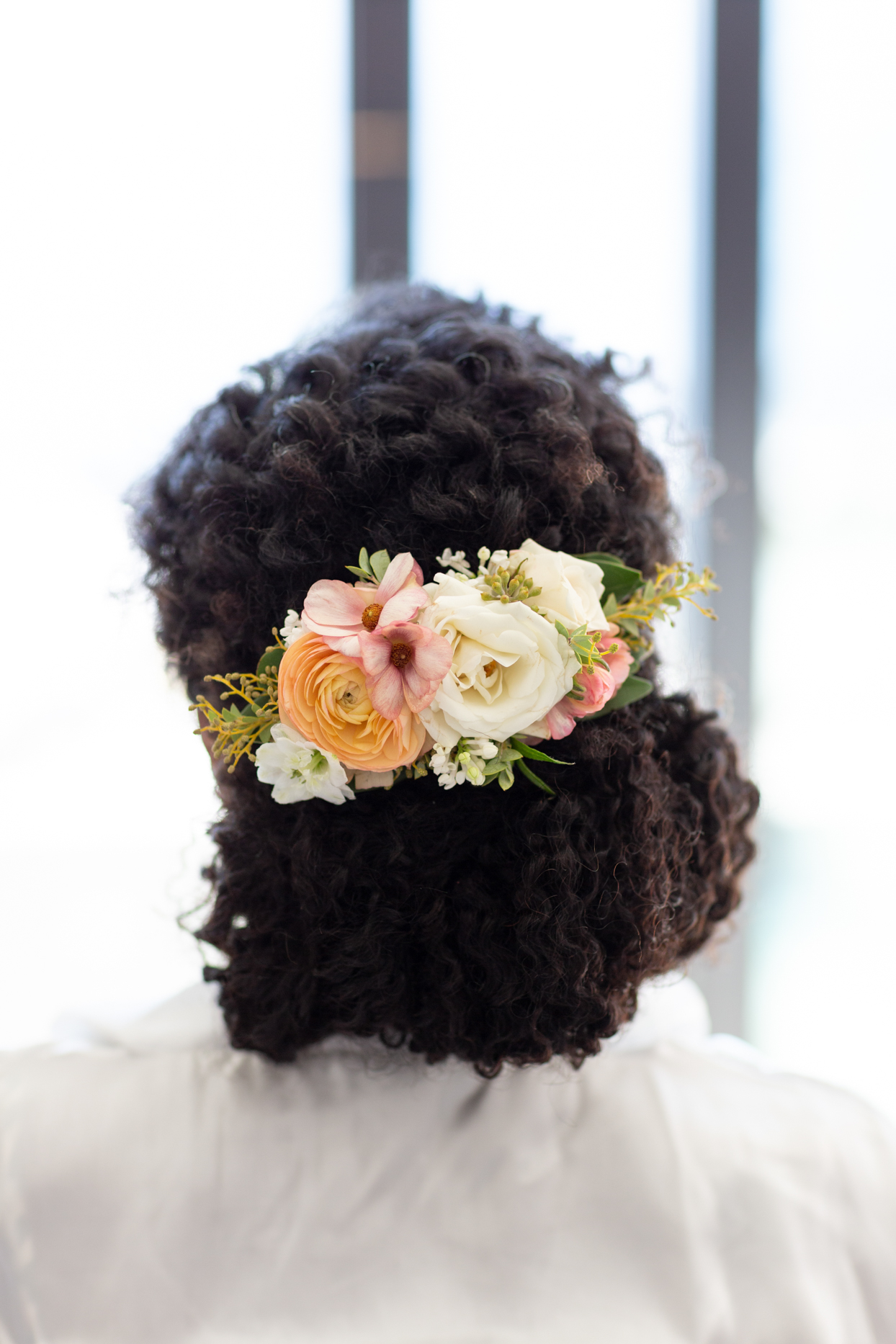 bride wearing hair in low bun with floral hair piece