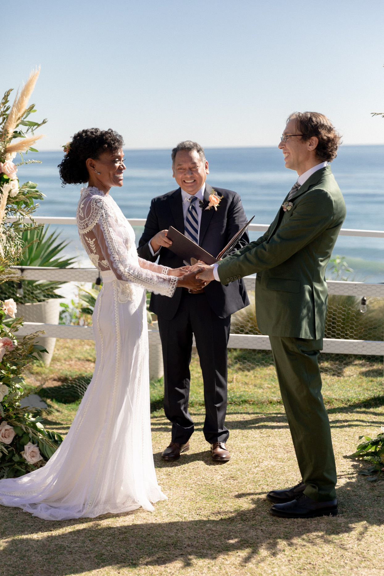 bride and groom smiling during ocean front wedding vows