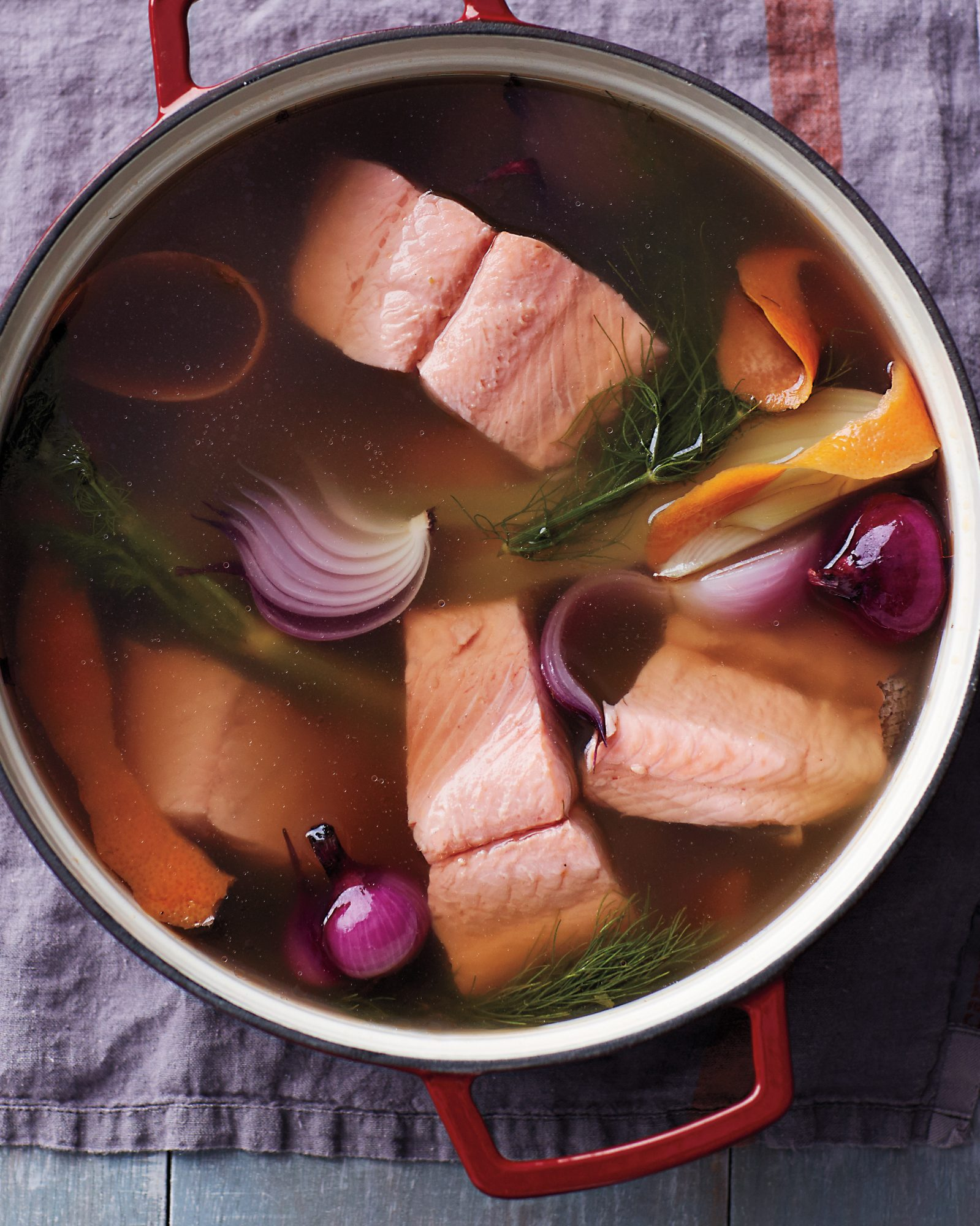 poached salmon in Dutch oven with cooking liquid and vegetables