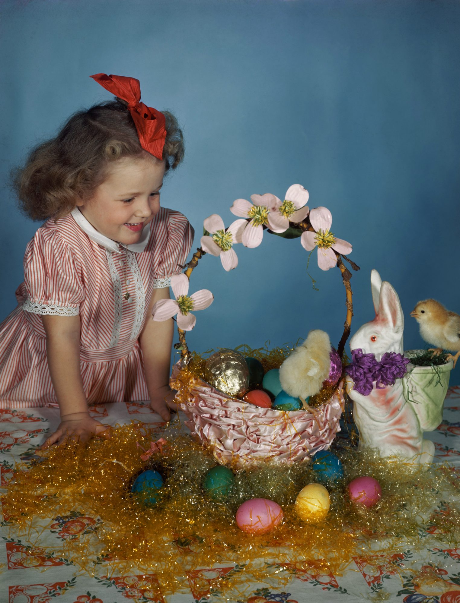 young girl with an Easter basket containing coloured eggs and fluffy chicks