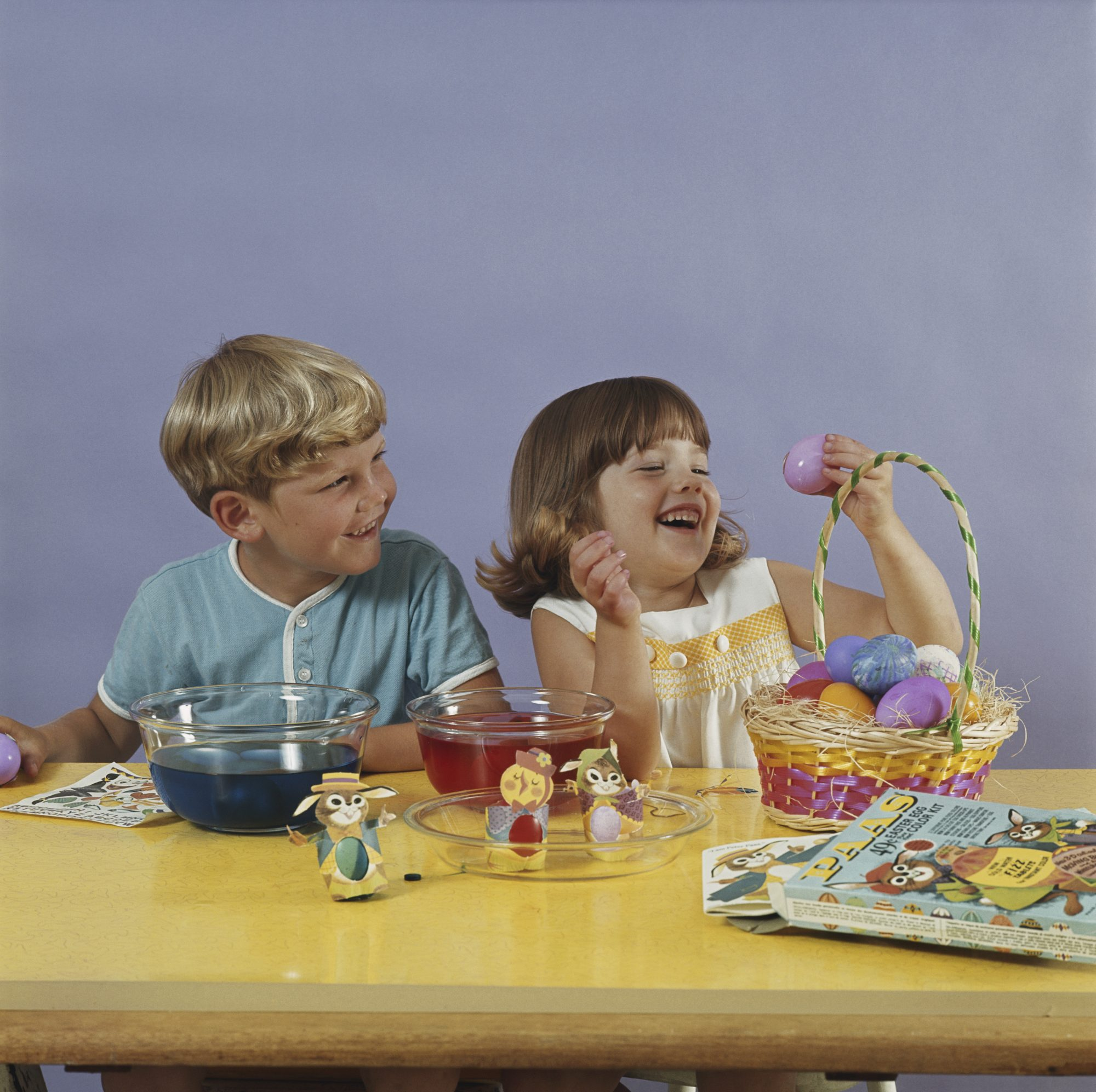 Children sitting at table with easter eggs smiling