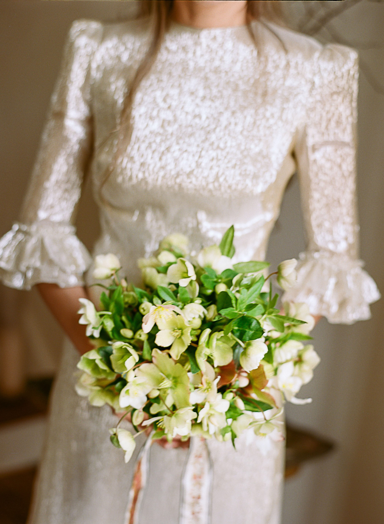 bride holding green and white hellebores wedding bouquet