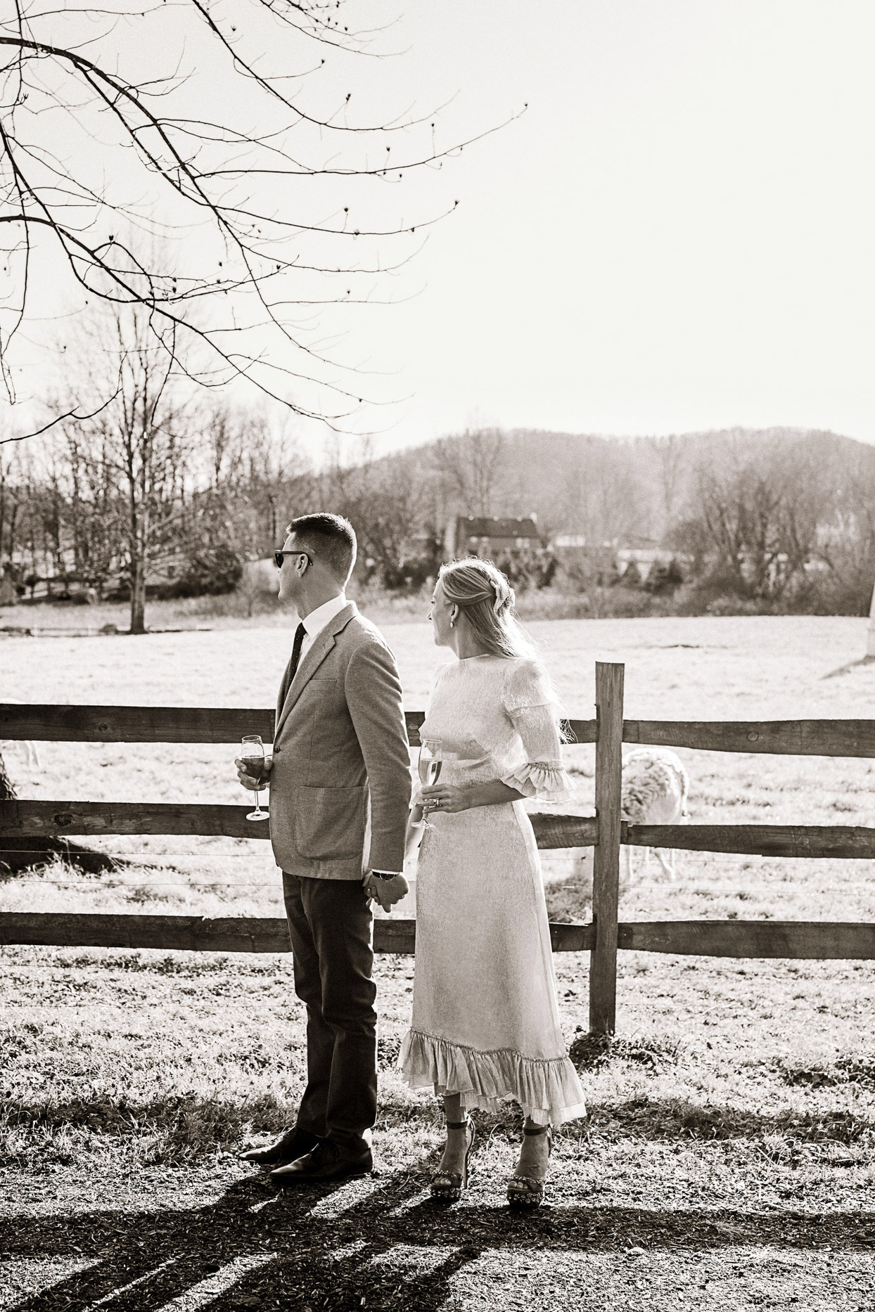 bride and groom hold hands next to wooden fence