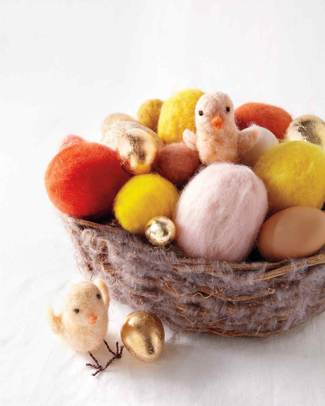 The downy softness of baby chicks is incredibly appealing, and you can replicate that inviting texture with wool roving: Use it to make little yellow chicks to adorn a twig basket. Begin by rolling yellow roving into a long oval shape; repeatedly poke all over it with a needle to felt. Add shape and density to the head, neck, and tail by poking those parts more. Once the desired shape is achieved, cover with another layer of the roving for a softer appearance. To make the wing, place the roving on the mat and poke with a needle. Attach to the body by poking at the front edge of the wing. Roll tiny bits of black roving and poke into the face for the eyes. Roll orange roving and poke into the face for the beak. Go over the floral wire with a marker. Cut two four-inch pieces, twist, and poke through the body for legs. Cut two more two-inch pieces and bend into small V's; twist onto the legs for the feet.                             Shop Now: Phinus Needle Felting Kit, $7, amazon.com; Woolbuddy Needle Felting Woolen Mat, $18, amazon.com; Panacea Green Floral Wire, $2.49, michaels.com.