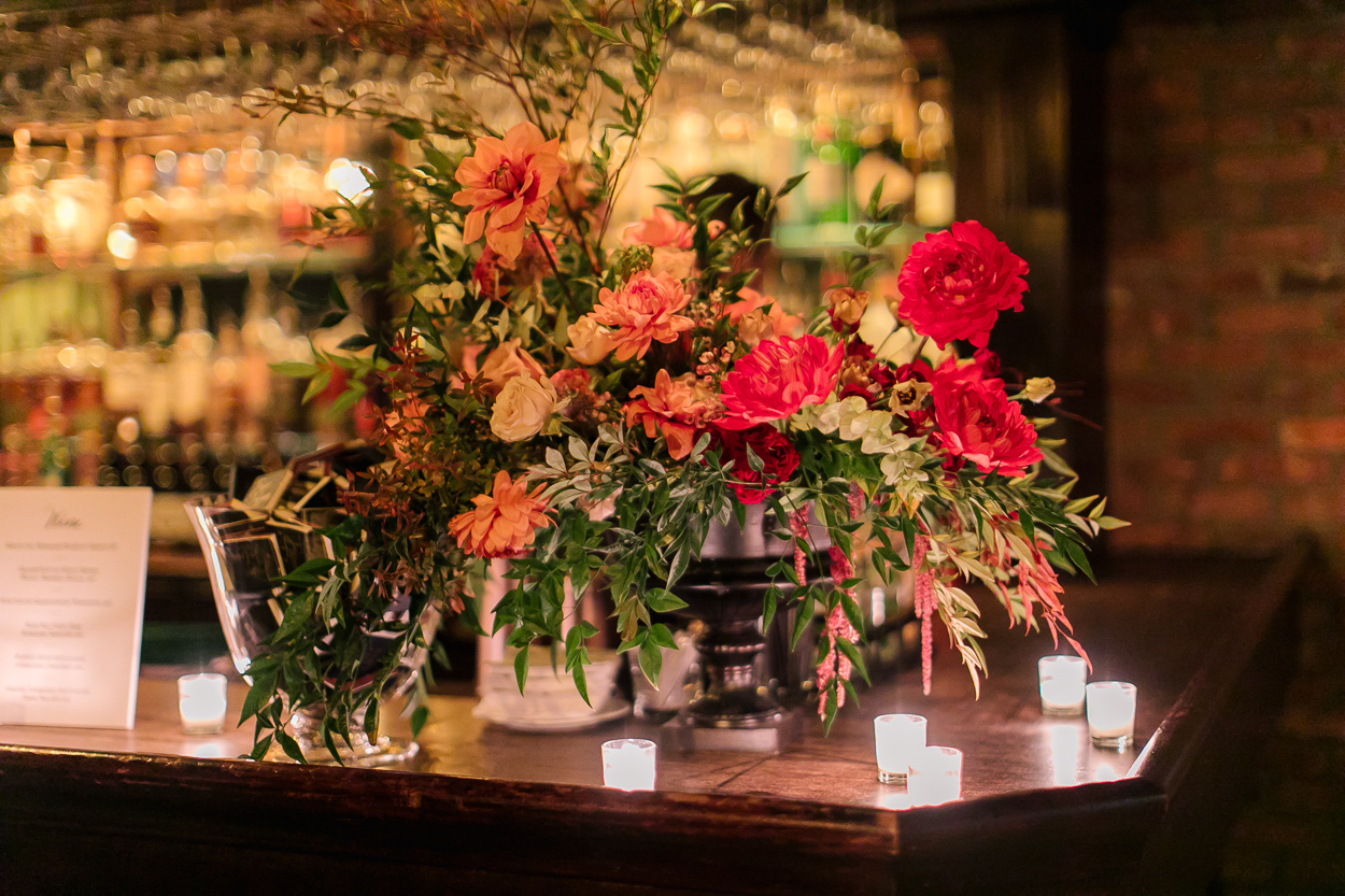 deep warm toned floral arrangements on wooden wedding bar