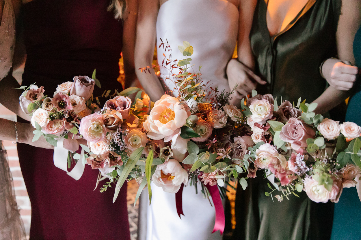 bridesmaids holding warm tone wedding bouquets