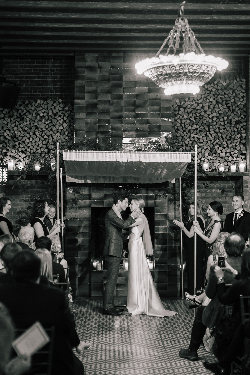 couple kissing under wedding chuppah at ceremony