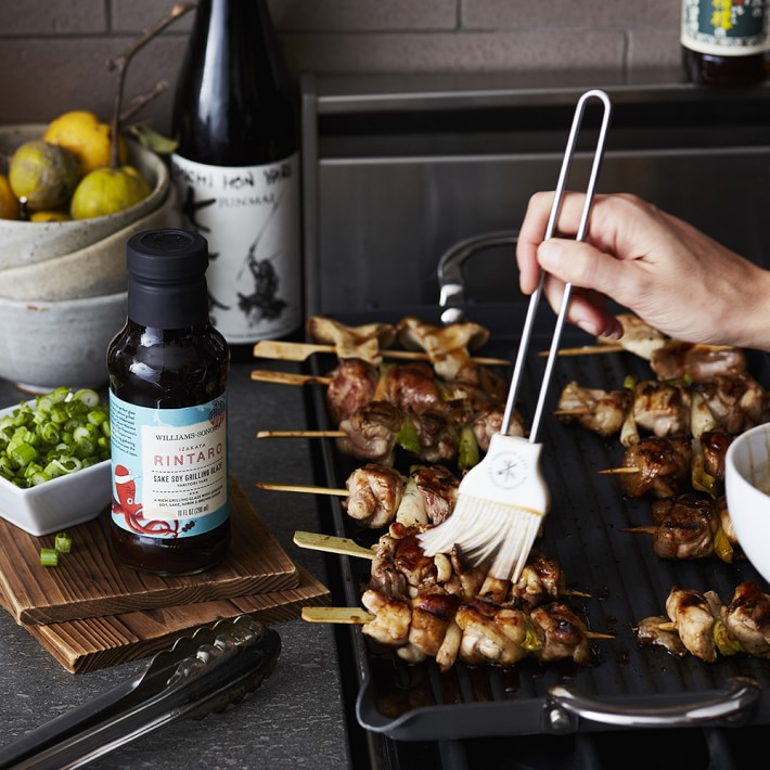 basting skewers over grill with silicone brush