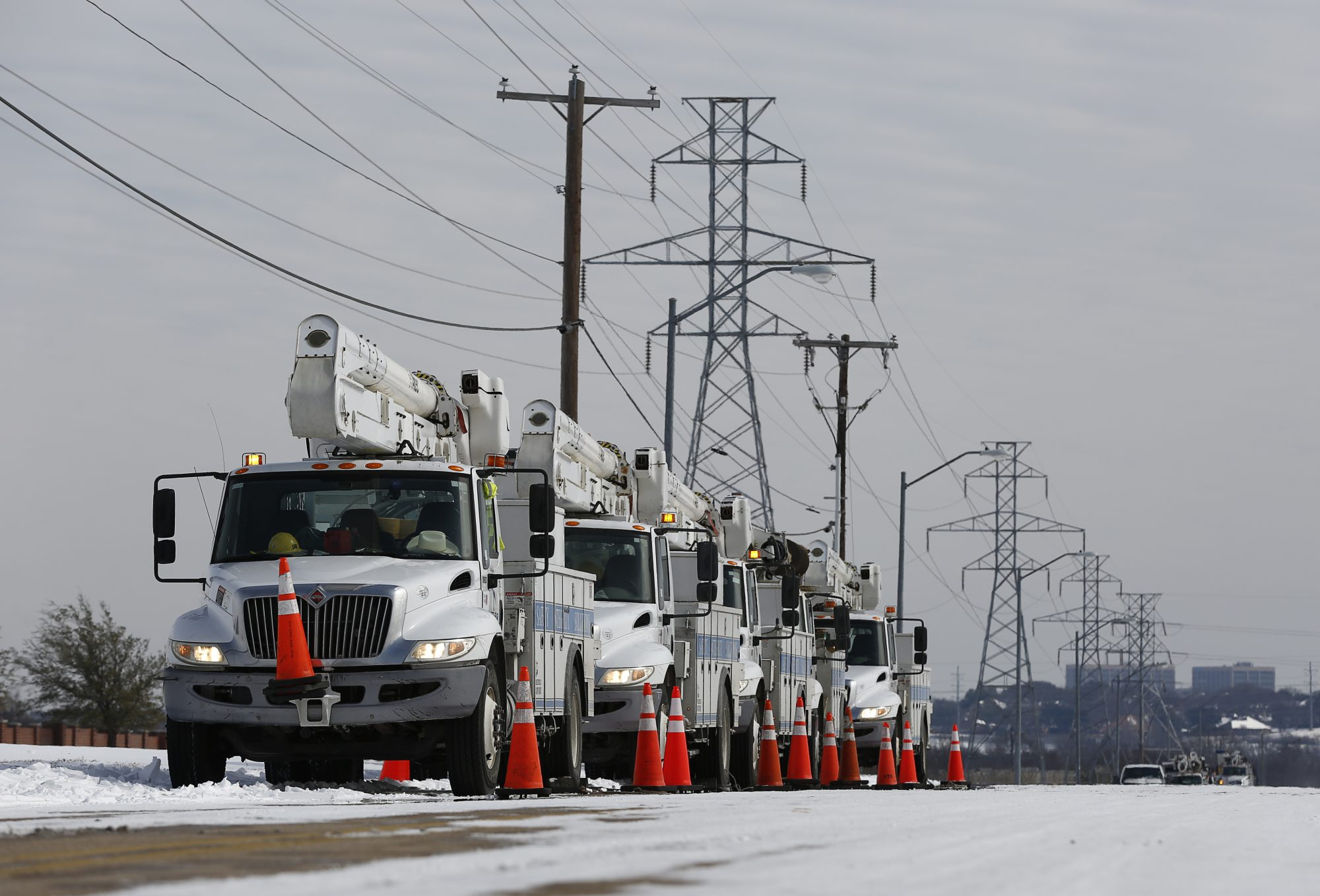 Electric Utility trucks are parked in the snow along the street