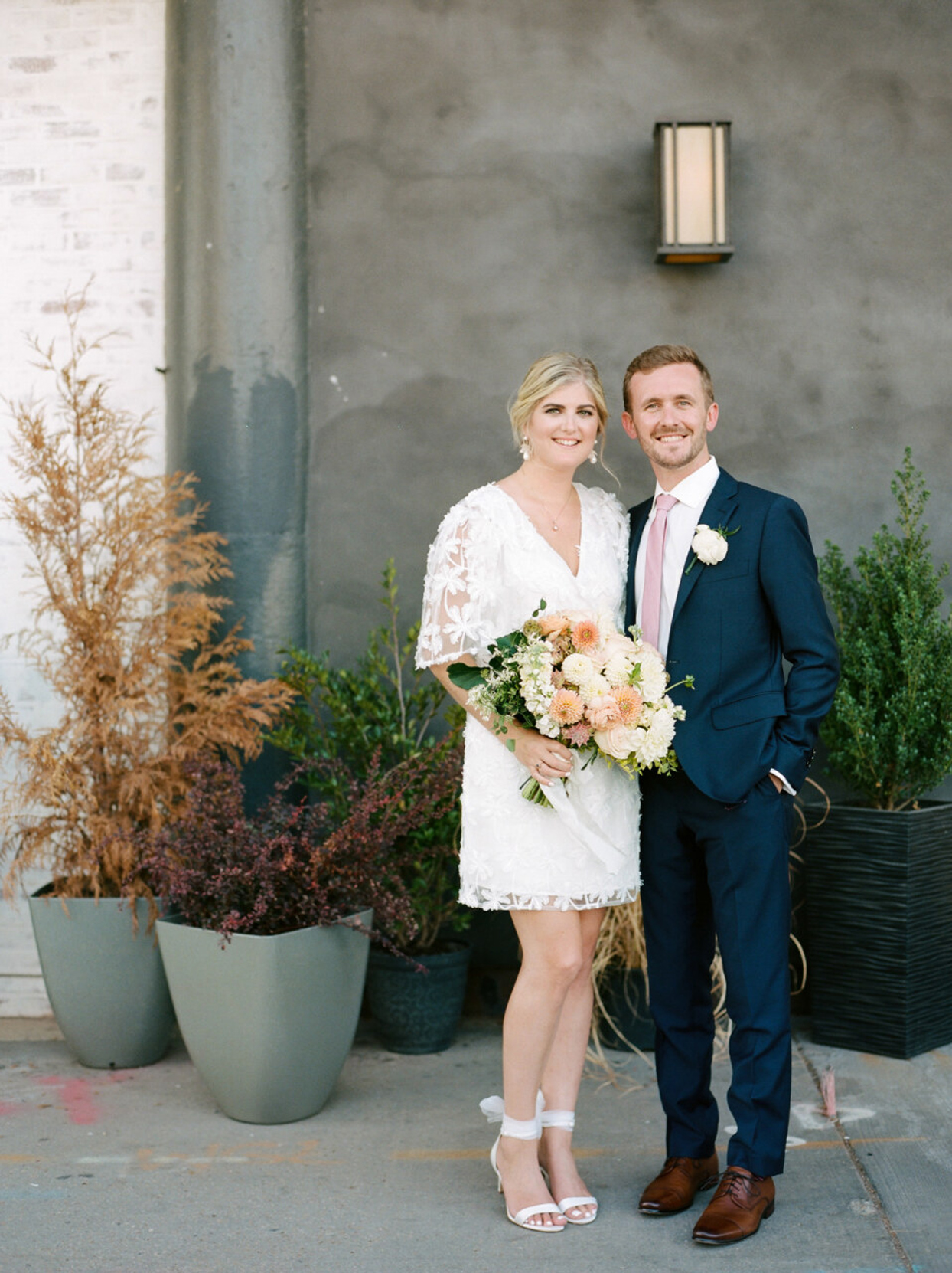 bride and groom posing by planters
