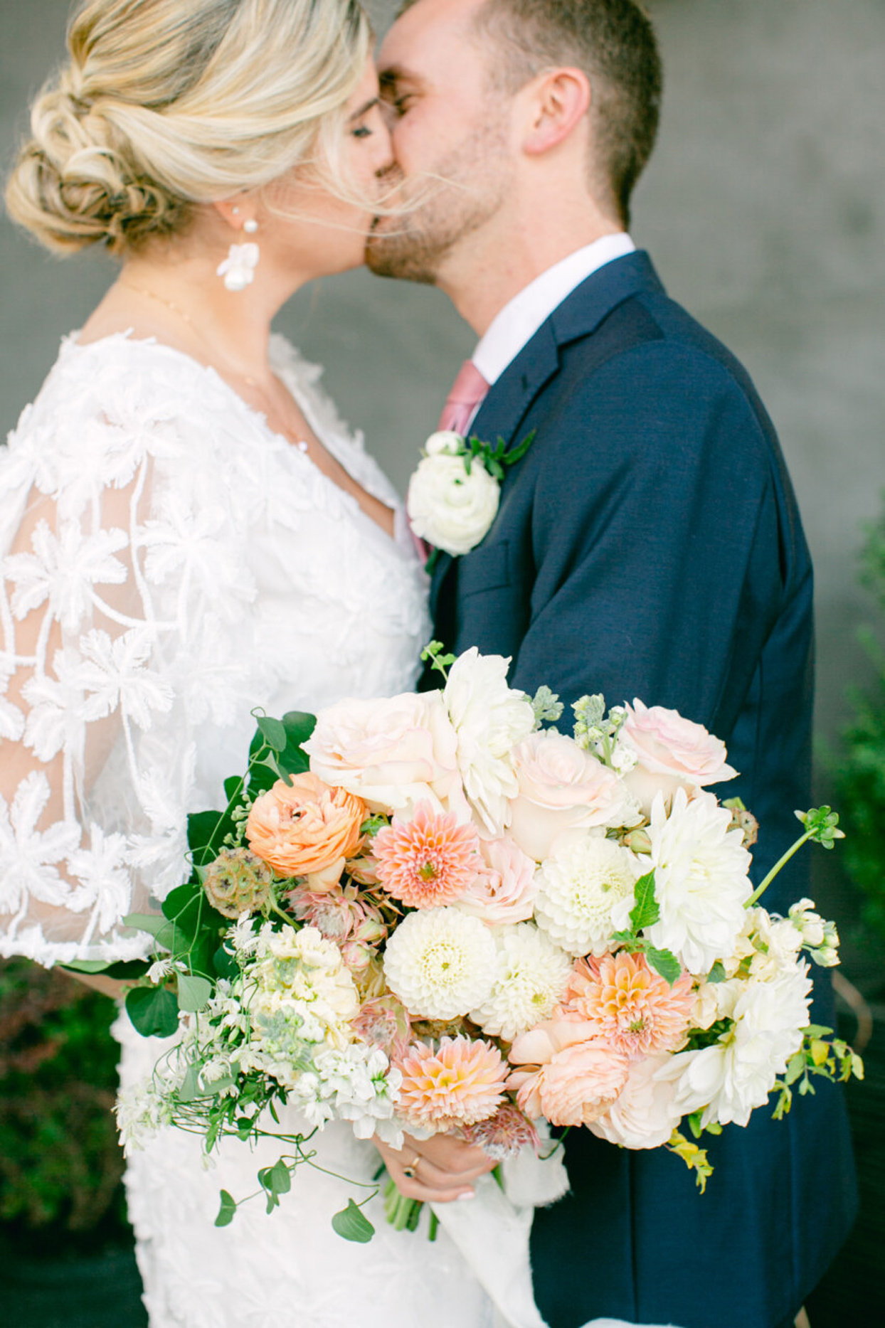 bride and groom kissing holding floral bouquet