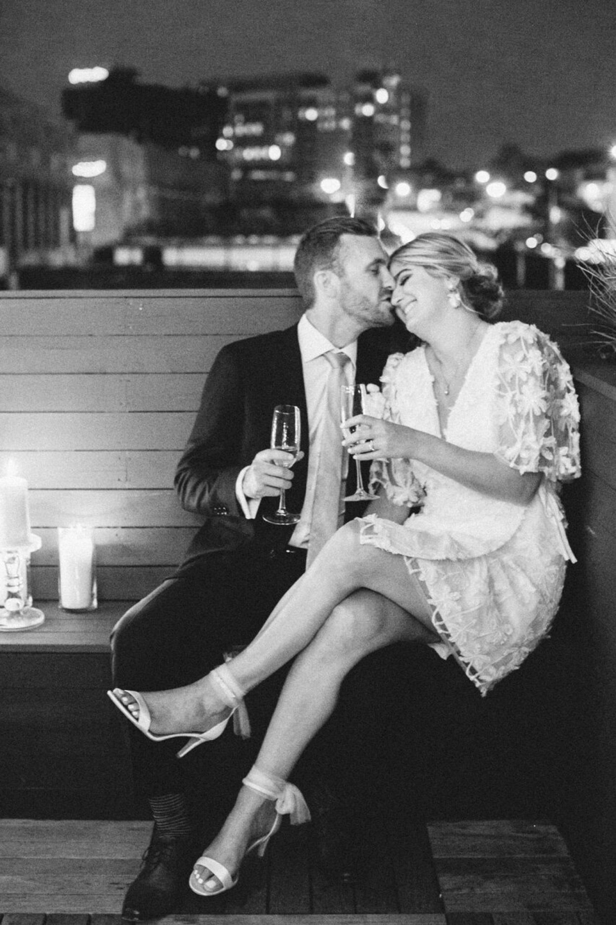 bride and groom holding champagne glasses on rooftop