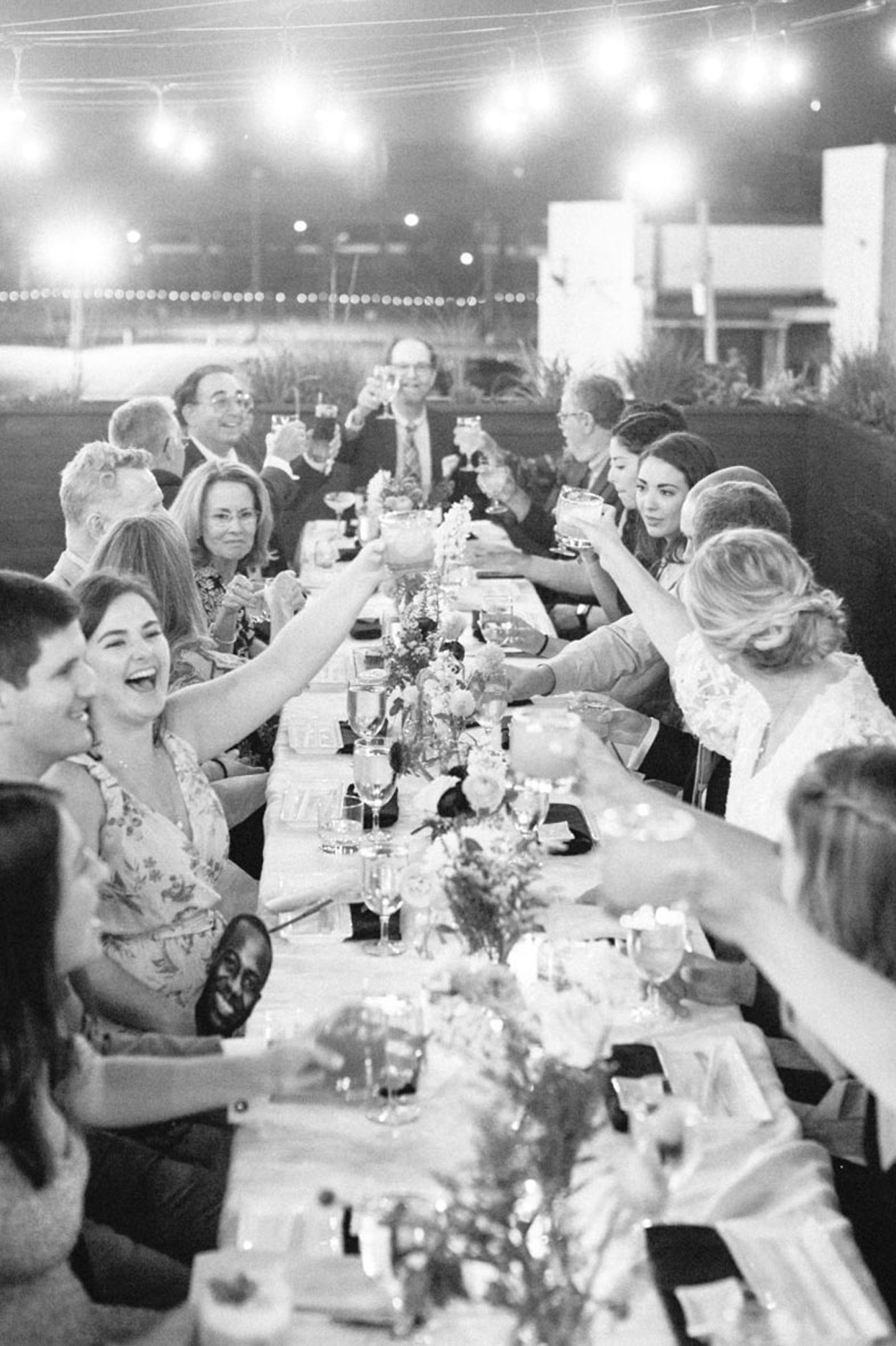 guests toast at long dinning table