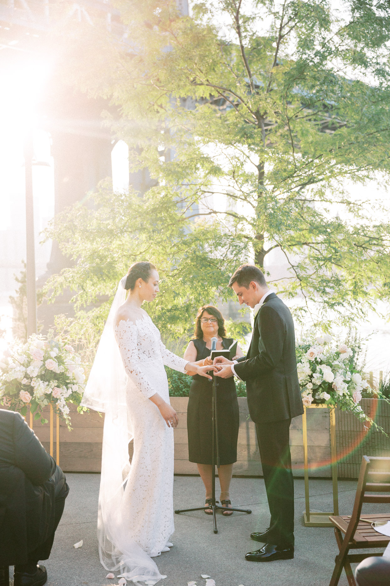 bride and groom exchanging rings with manhattan bridge backdrop