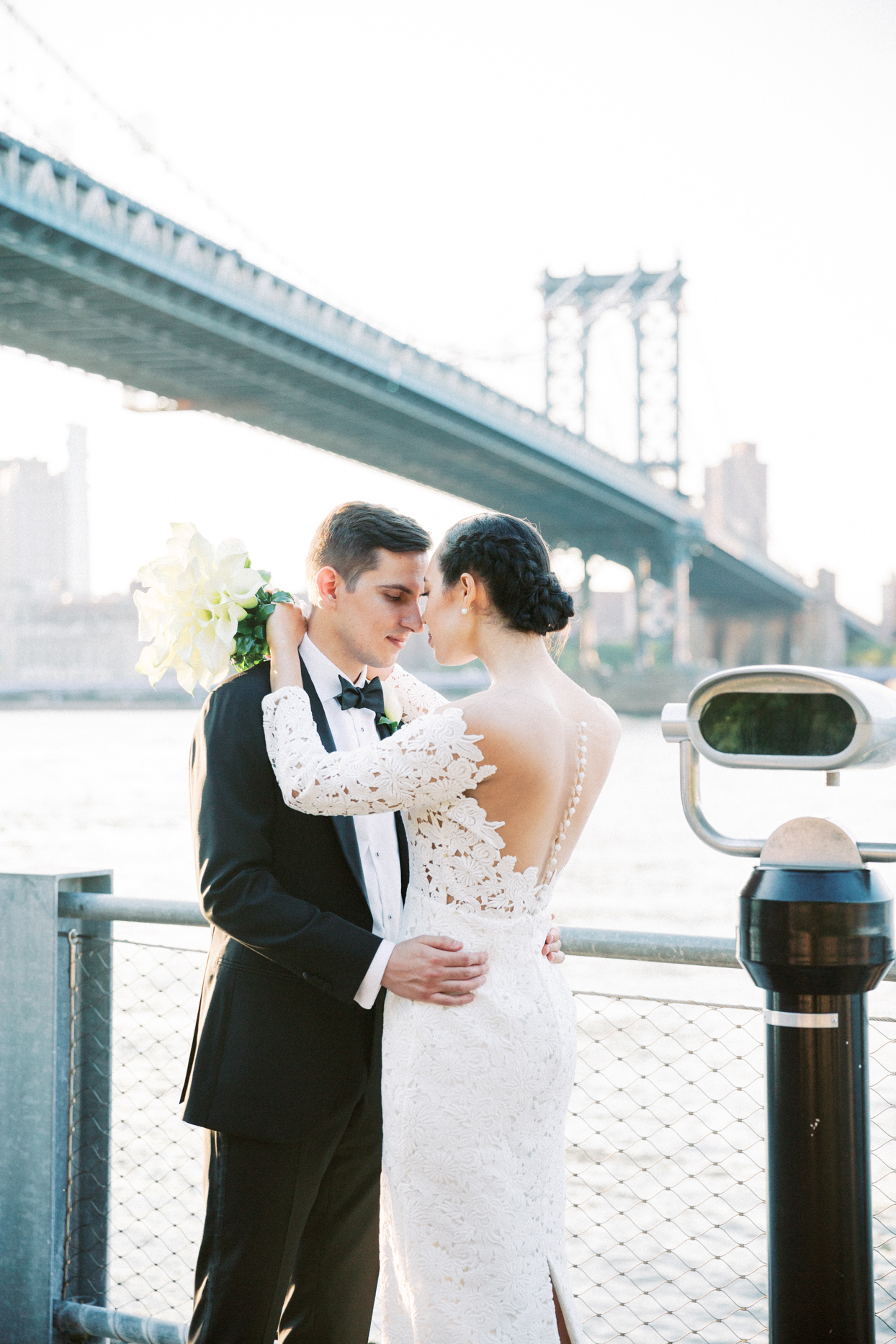 wedding portrait against fence overlooking east river