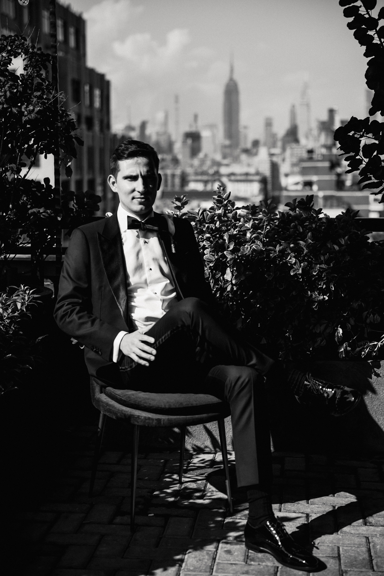 moody portrait of groom sitting with new york city backdrop