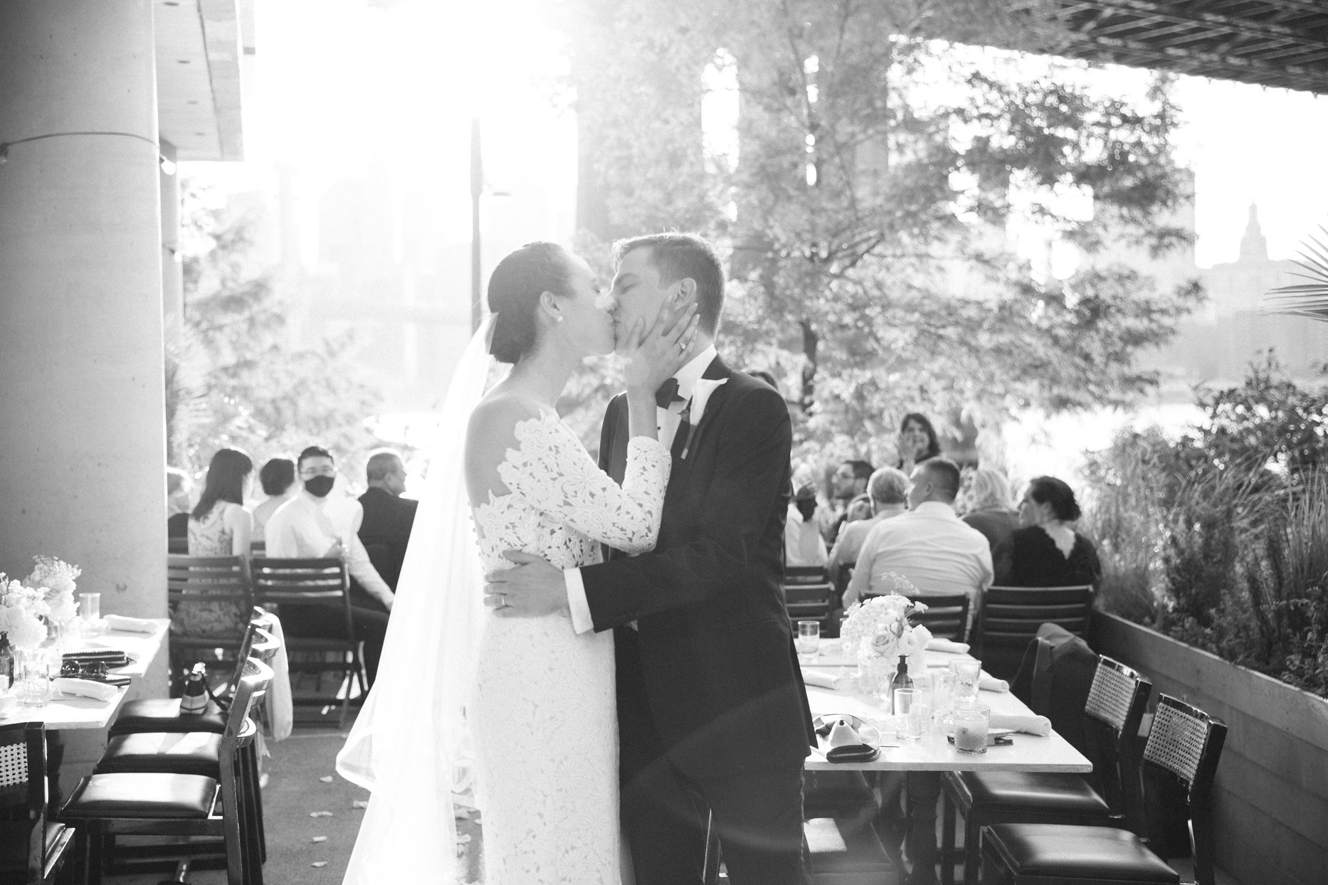 couple kissing with guests sitting in ceremony chairs behind