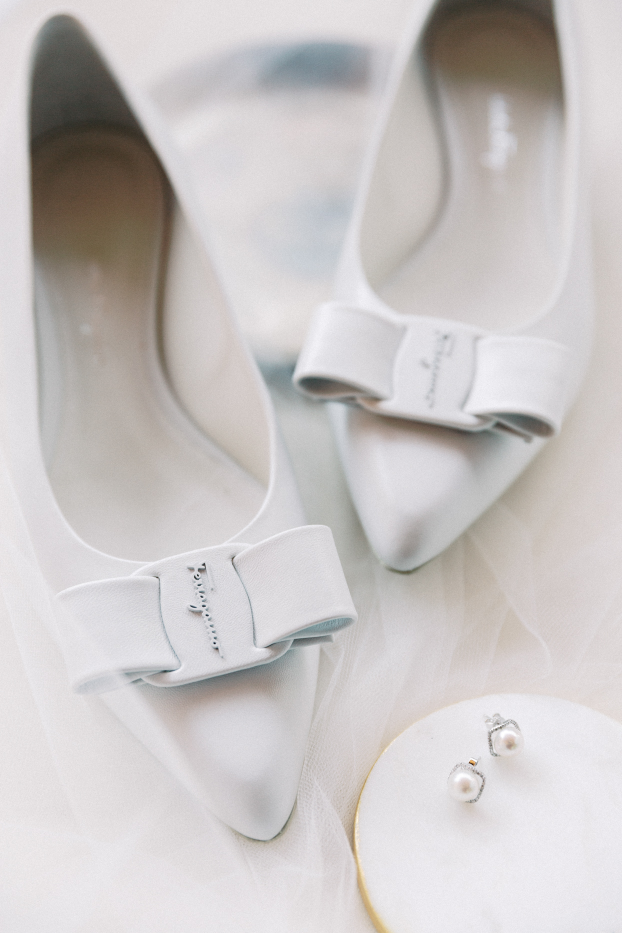 bride's white heels and pearl earrings for wedding