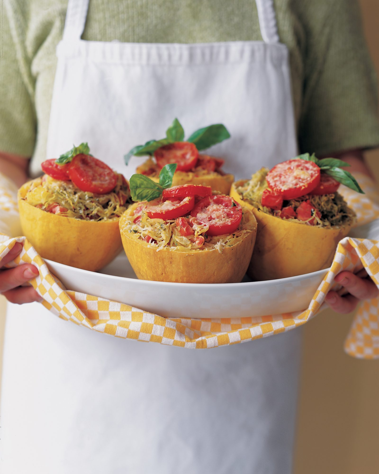 Halved spaghetti squash are filled with the best ingredients from the farmers' market and then baked for a dramatic entrée that sings of summer.