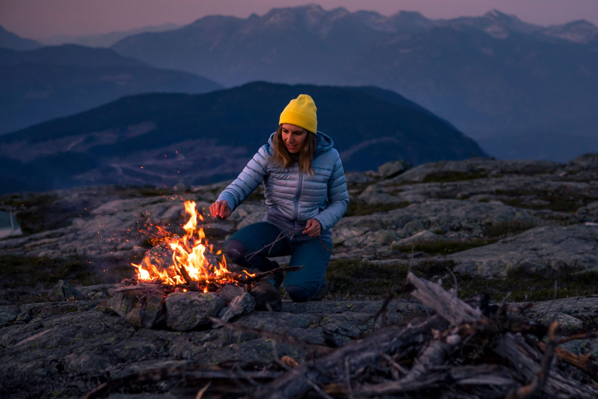 woman lighting campfire on a mountain at dusk