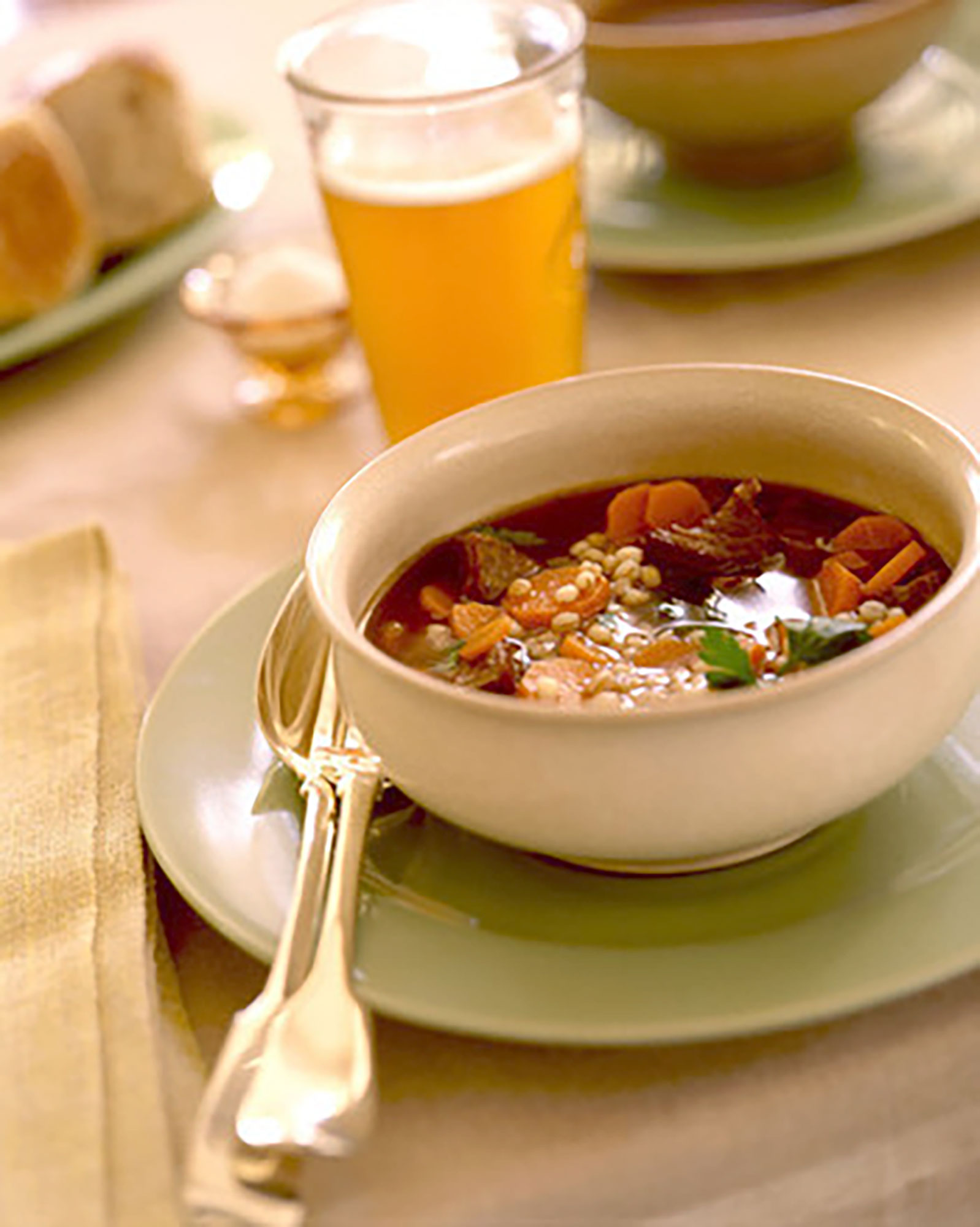 bowl of beef and barley soup with glass of beer