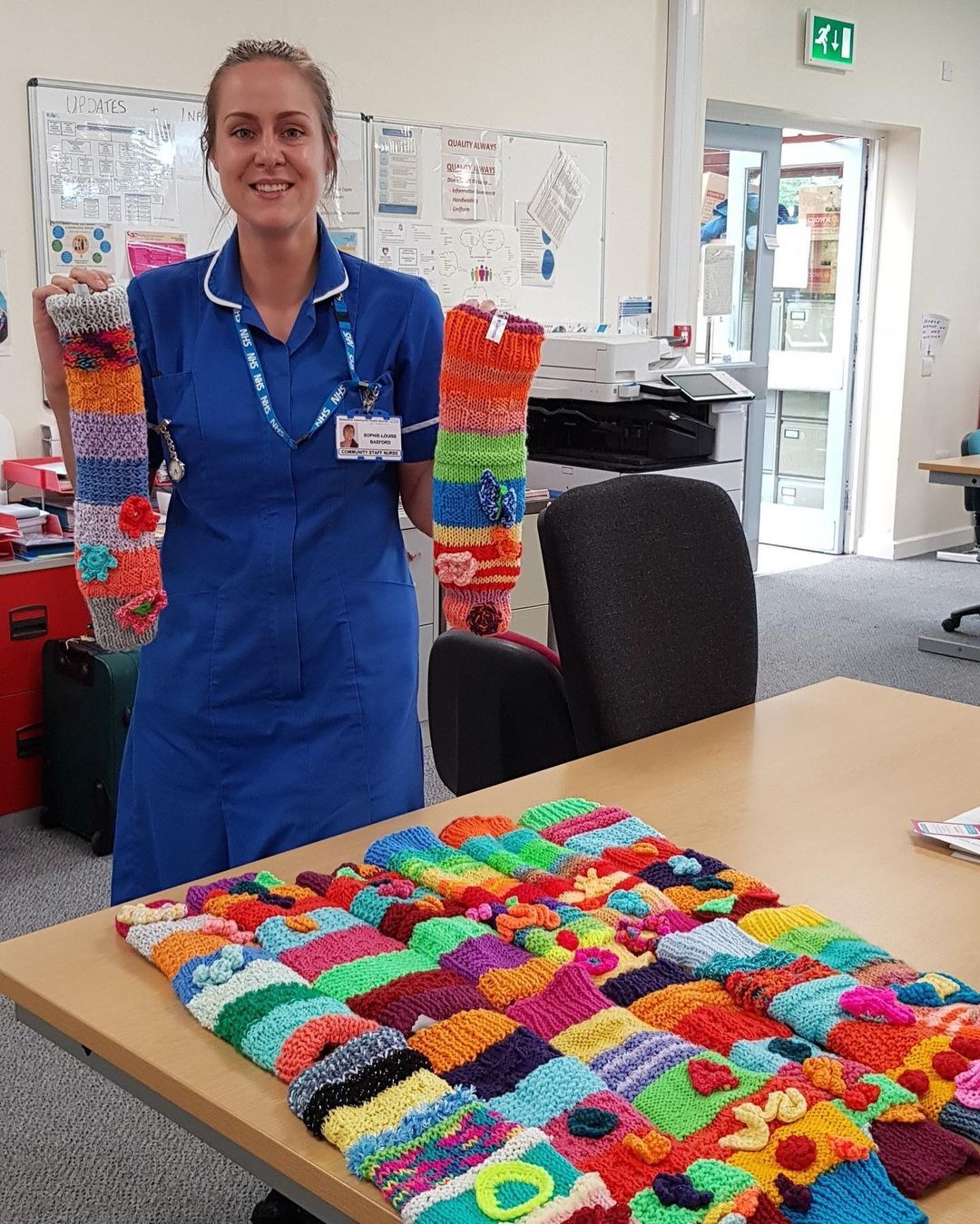 nhs nurse holds up hand knitted fidget sleeves