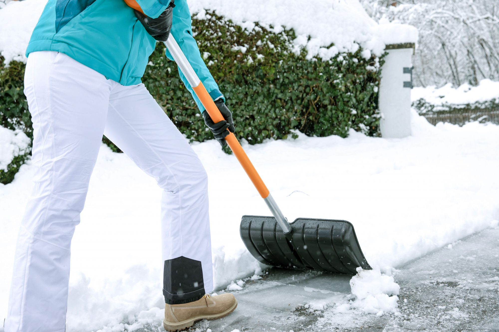 person shoveling snow in winter clothes