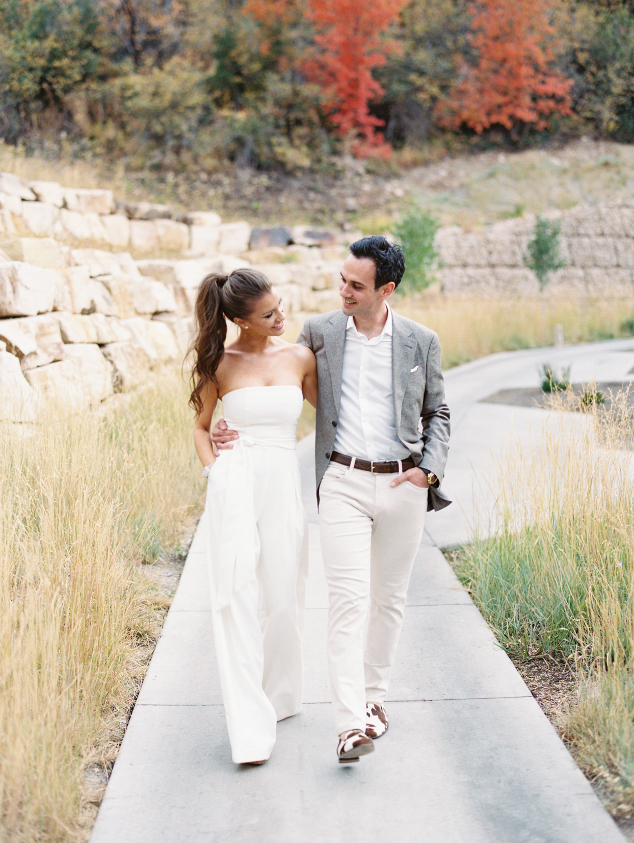 bride and groom smile holding each other while walking on pathway