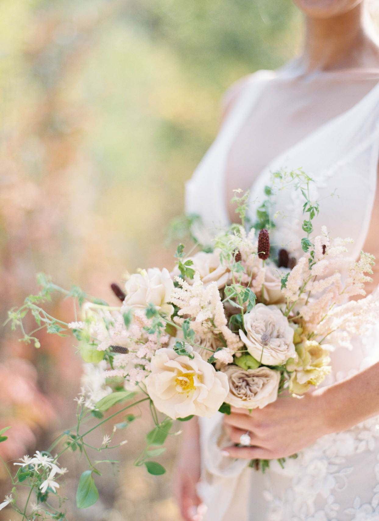 bride holding earth toned floral wedding bouquet