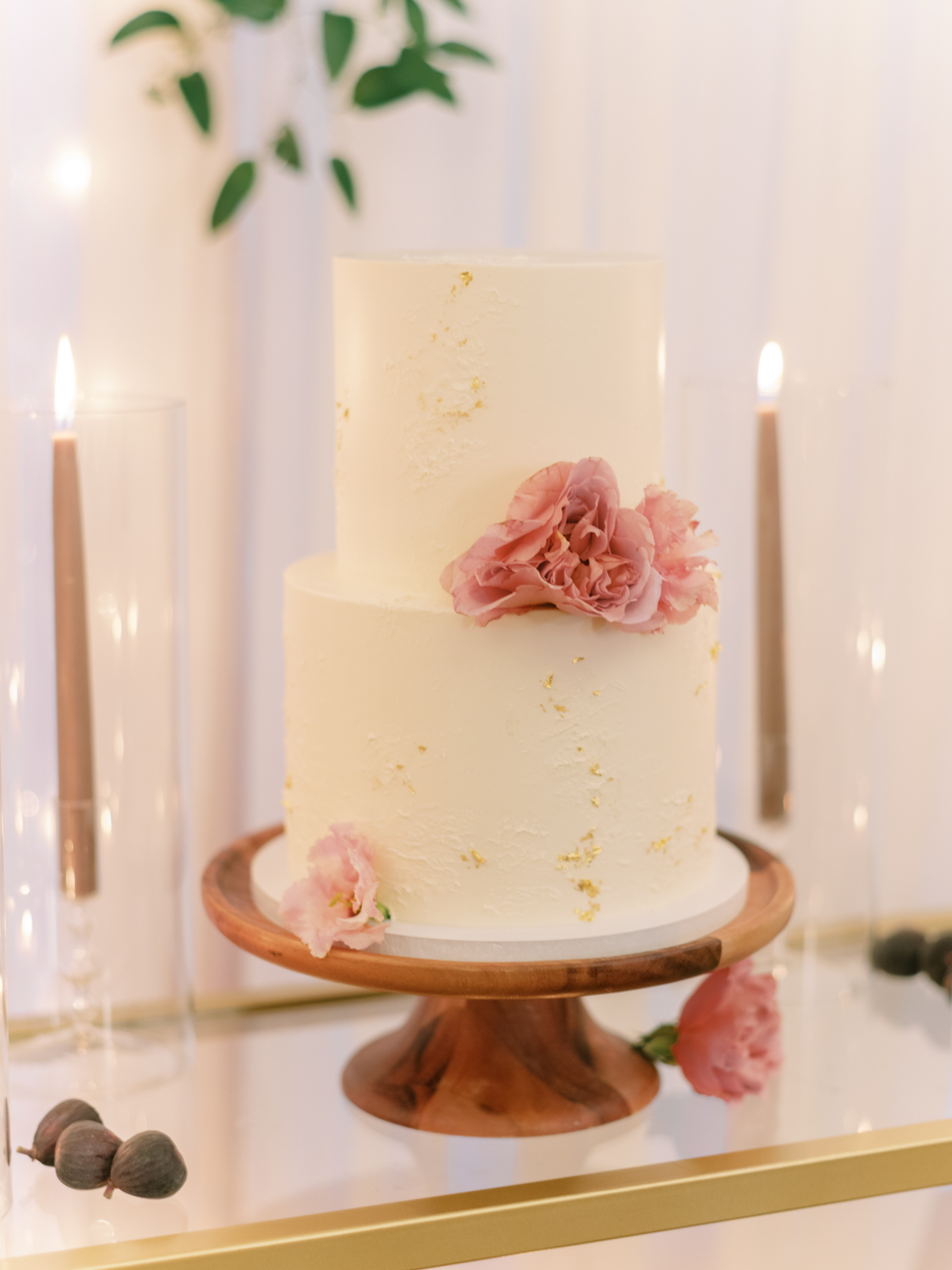 two tier white frosted wedding cake with gold foil and pink floral accents