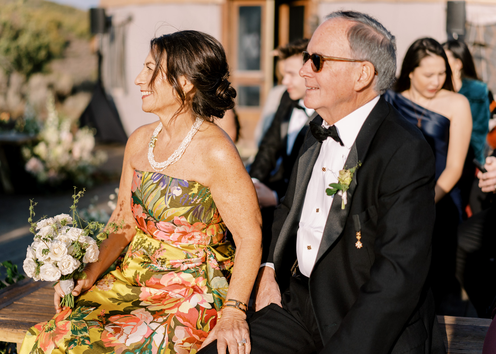 parents of bride and groom sitting on wedding ceremony bench