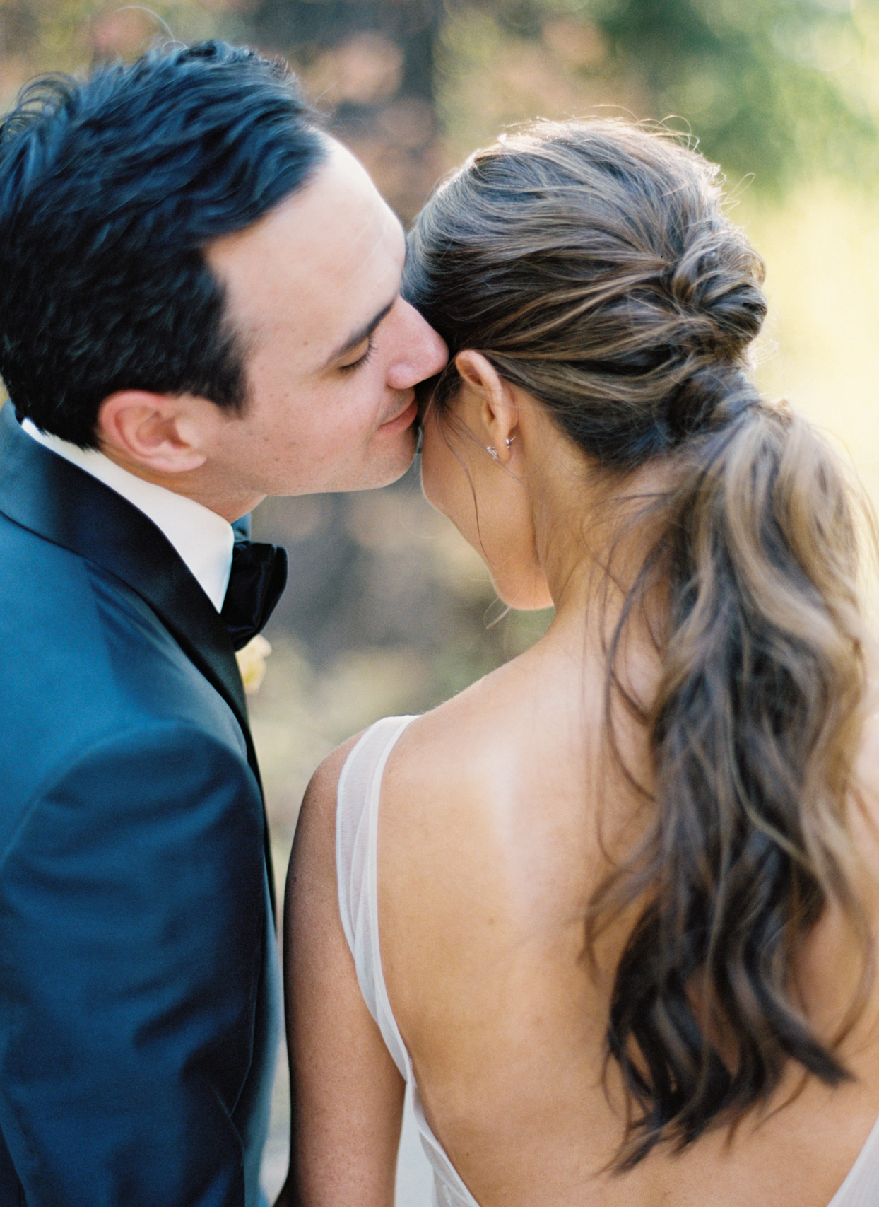 groom leans into bride outside