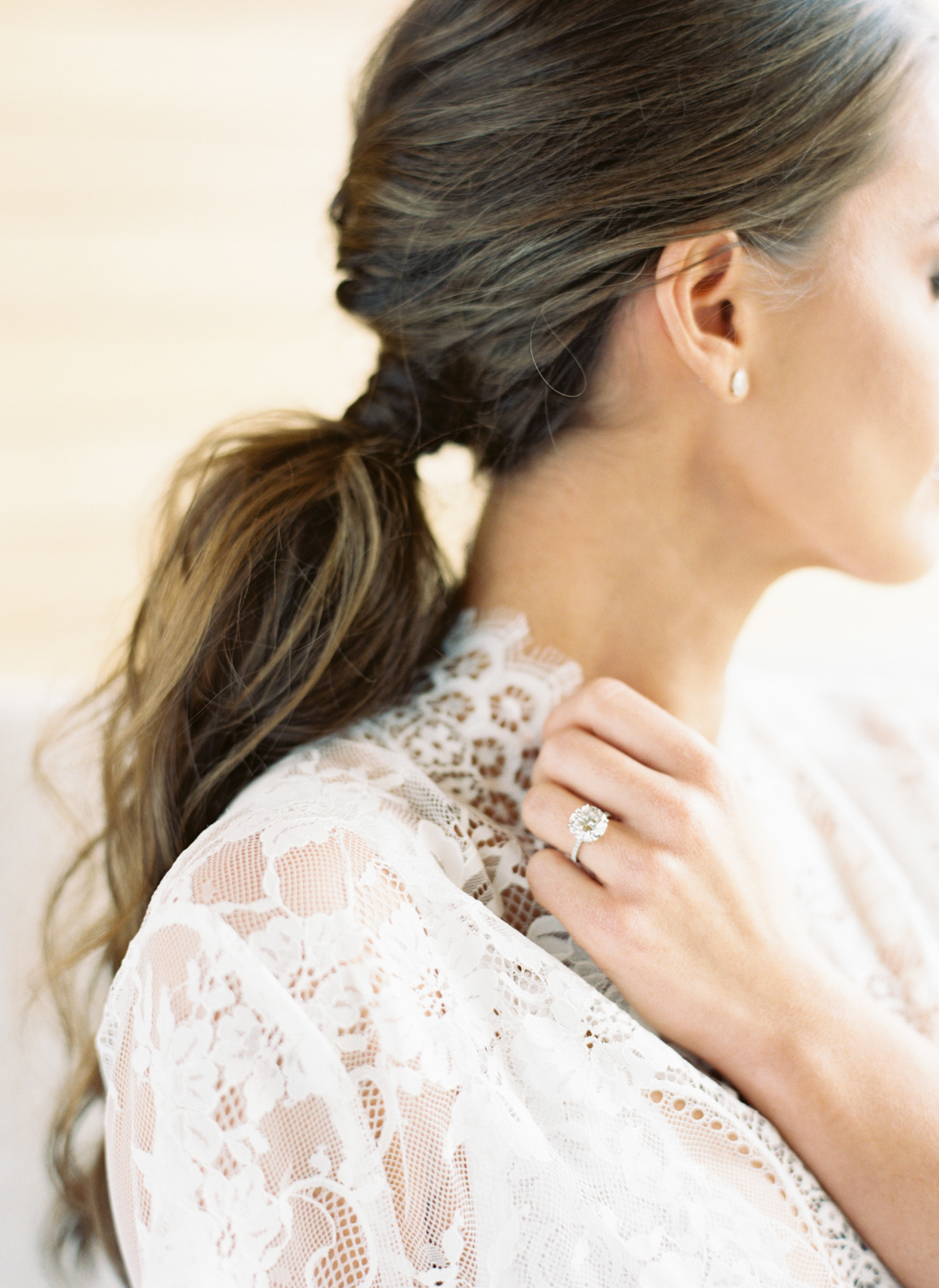 bride with hair in low ponytail wearing engagement ring