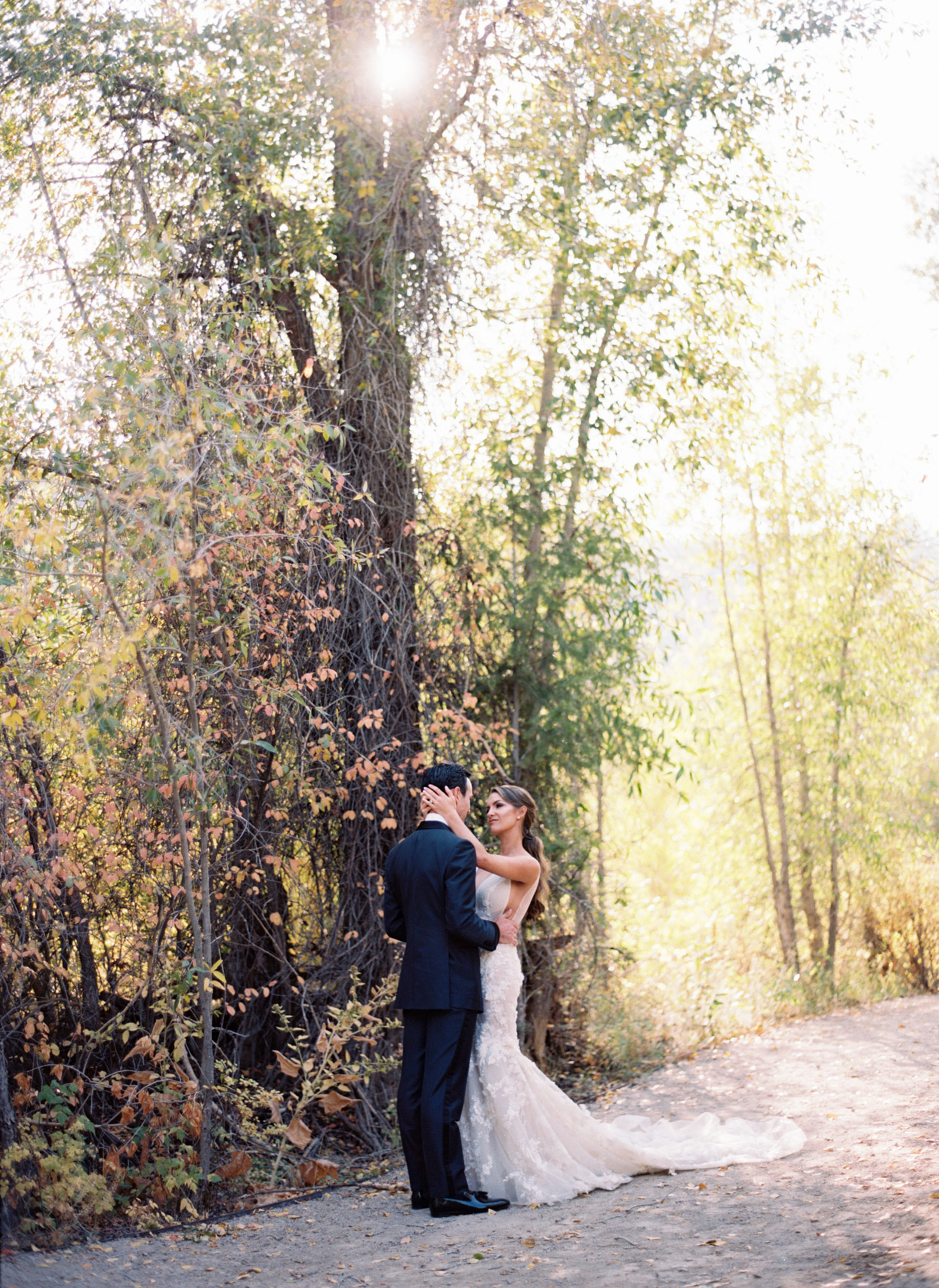 bride and groom embrace looking at each other on outdoor pathway